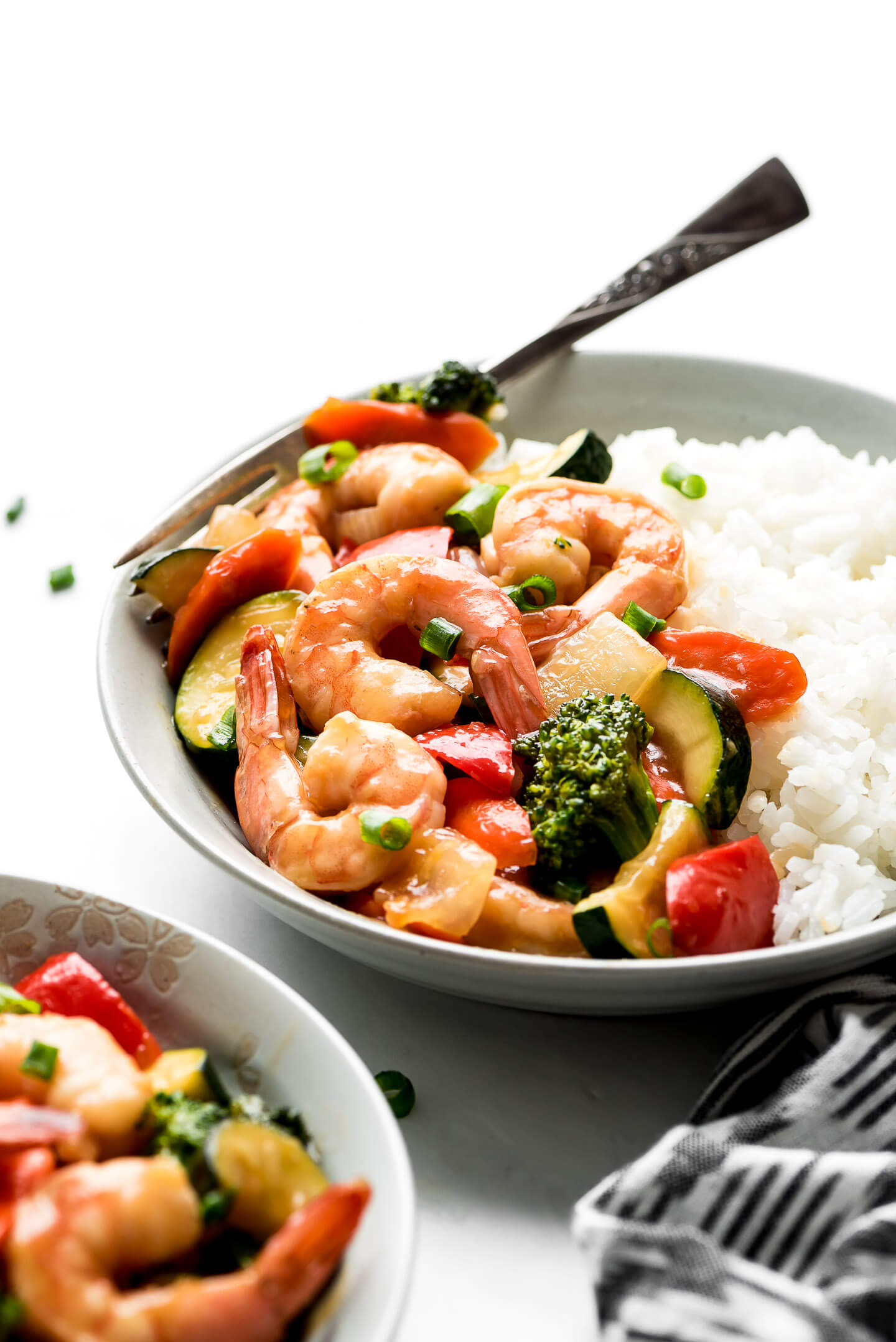 A close up shot of Shrimp Stir Fry in a bowl with rice.