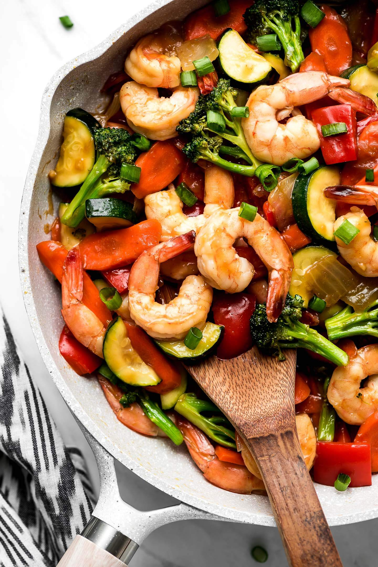 Close up shot of Shrimp Stir Fry in a pan with a wooden spoon about to lift some out.