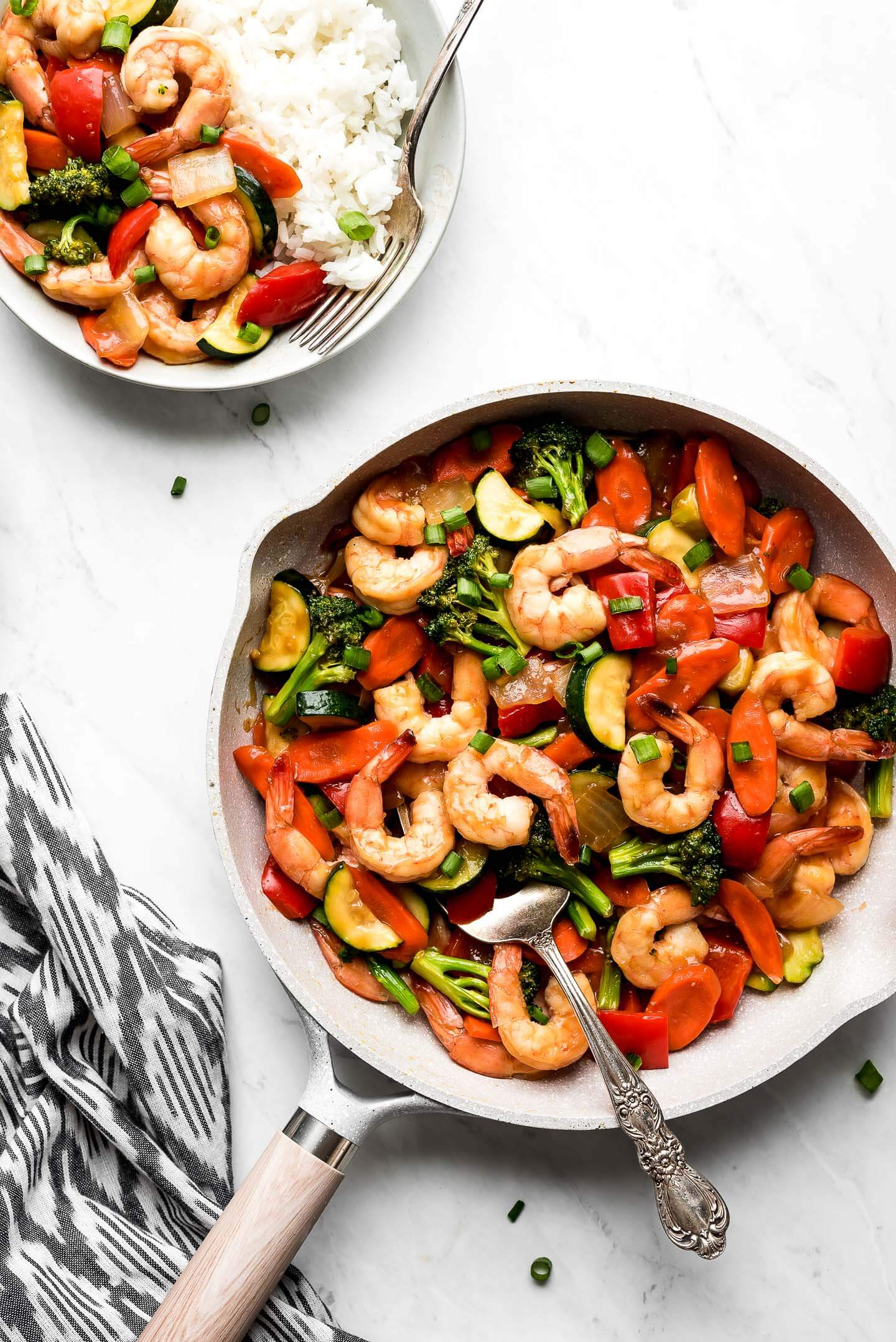 A skillet of Shrimp Stir Fry and a bowl of rice with stir fry.