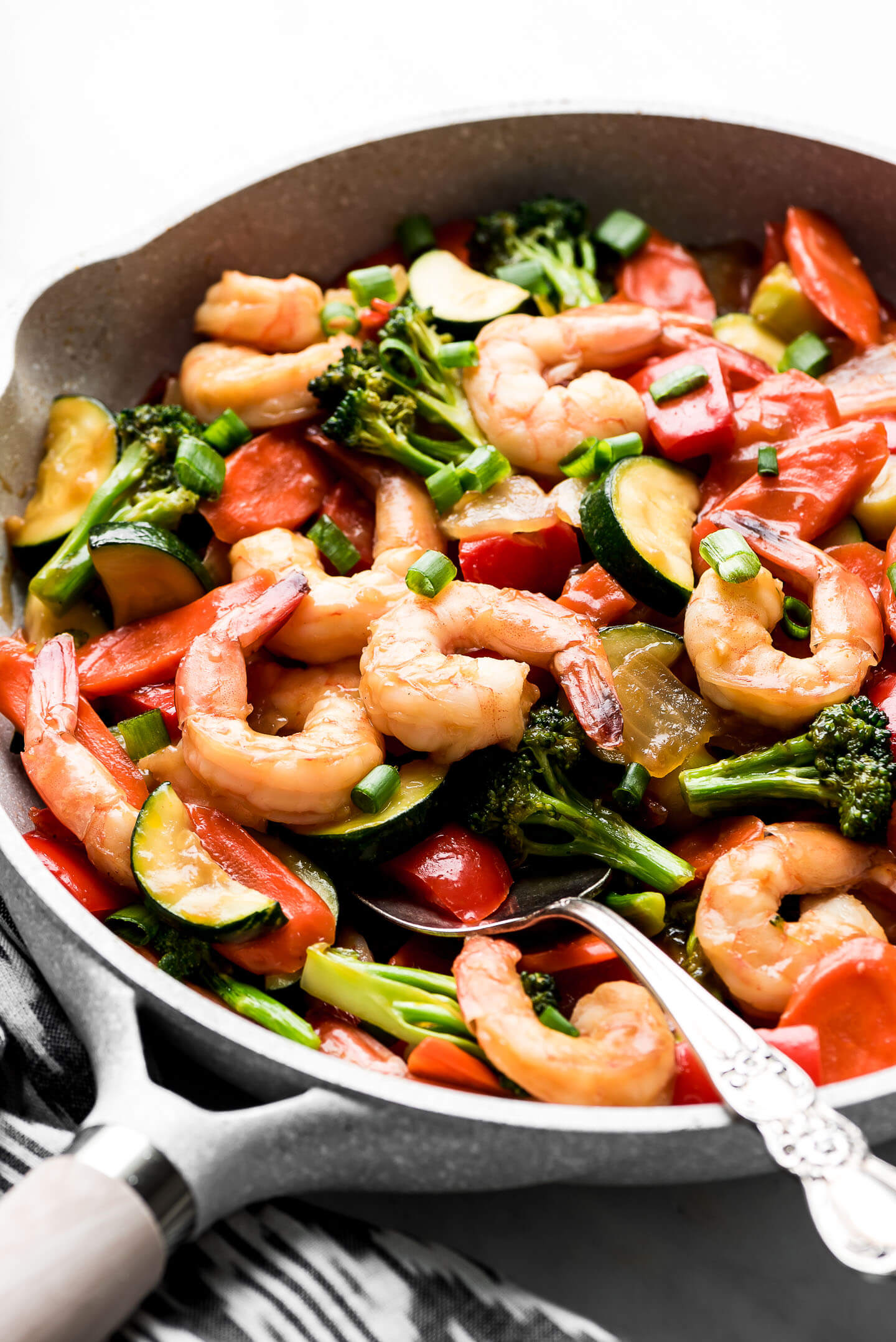 A skillet full of Shrimp Stir Fry and a serving spoon in the side.