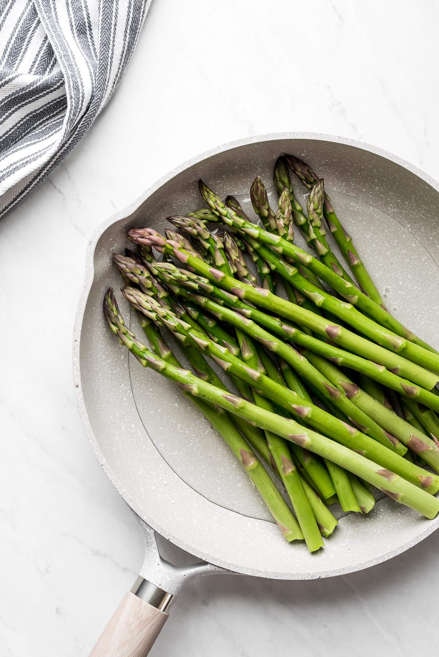Fresh Asparagus spears in a skillet with water.