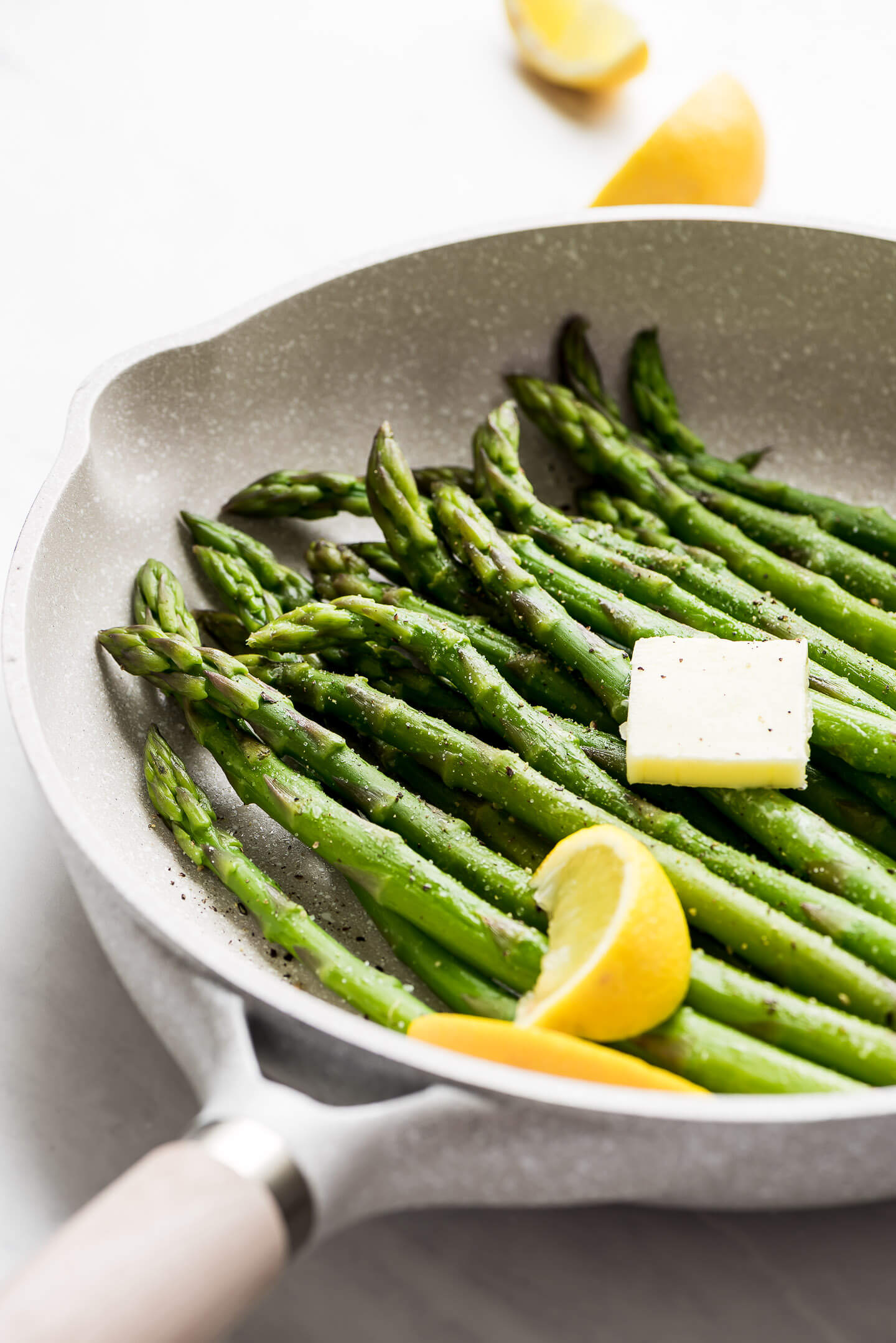 Steamed Asparagus in a skillet with a pat of butter on top and lemon wedges.