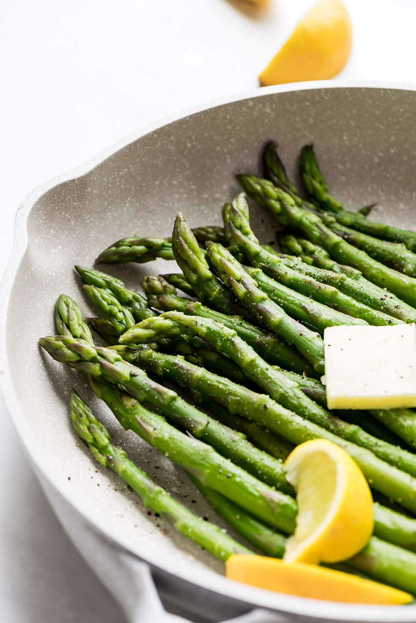 A close up shot of steamed asparagus spears in a pan seasoned with salt and pepper, a pat of butter, and lemon wedges.