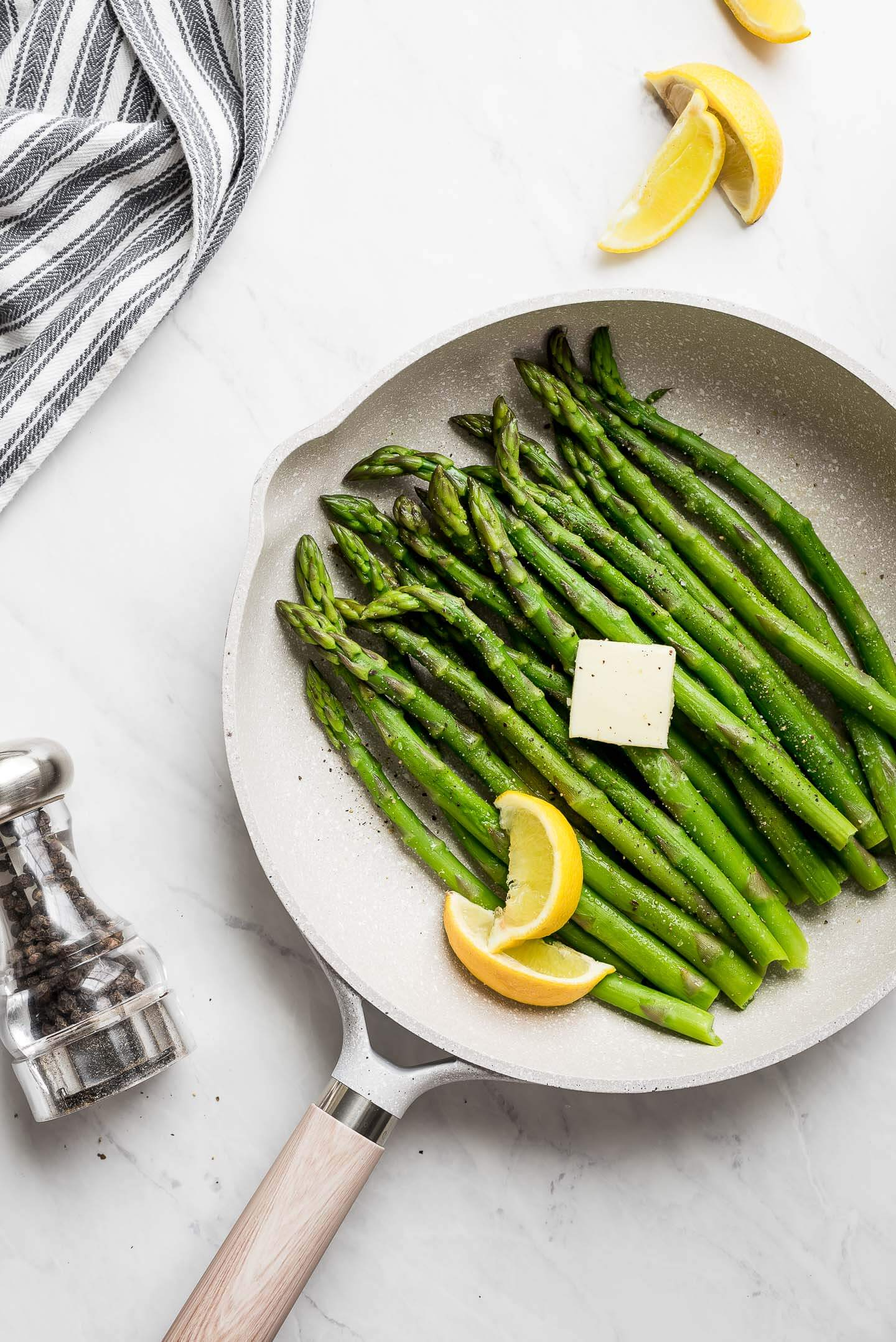 Stovetop asparagus in a skillet, seasoned with salt and pepper, a pat of butter, and lemon wedges.