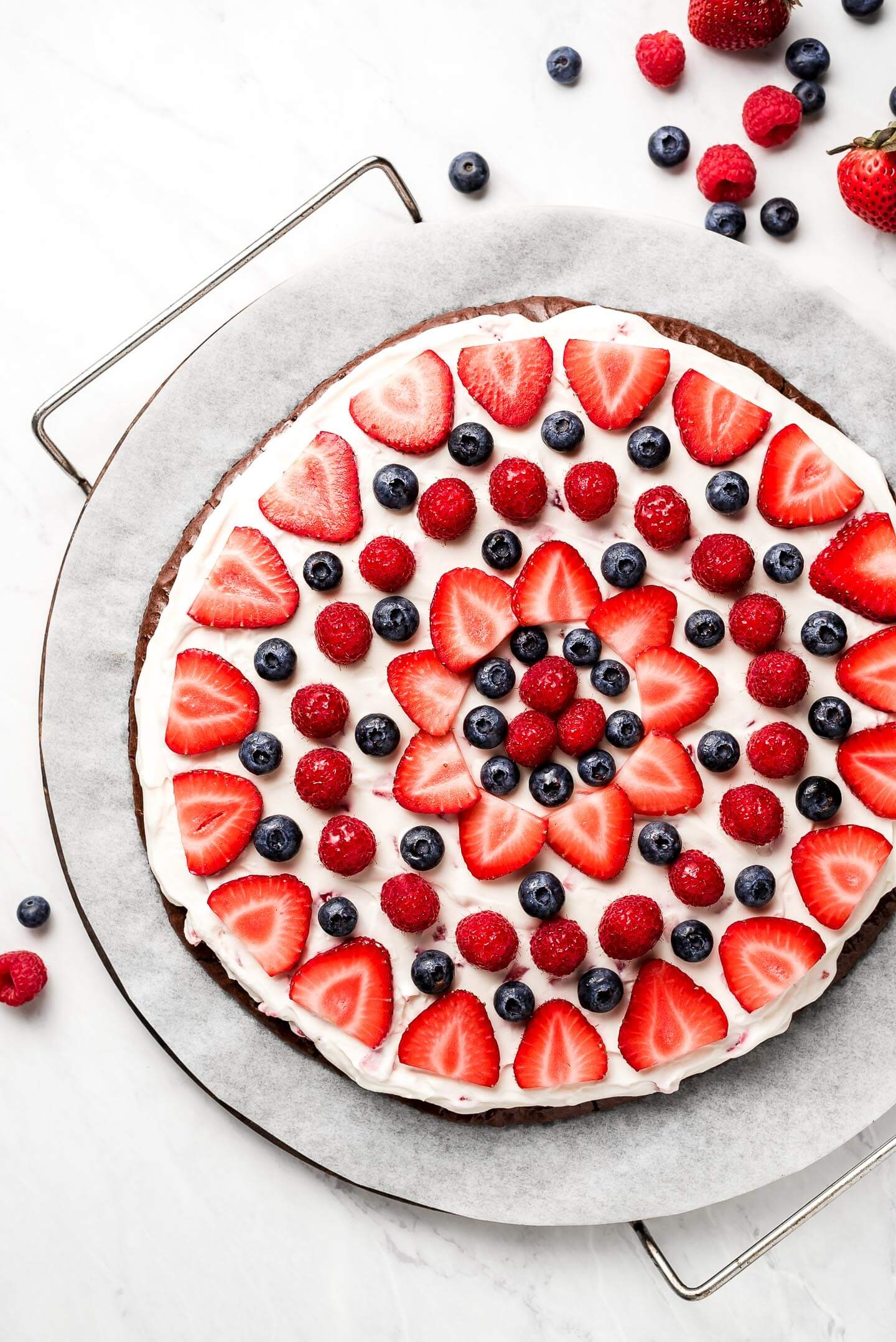 A brownie fruit pizza on a parchment lined pizza stone.