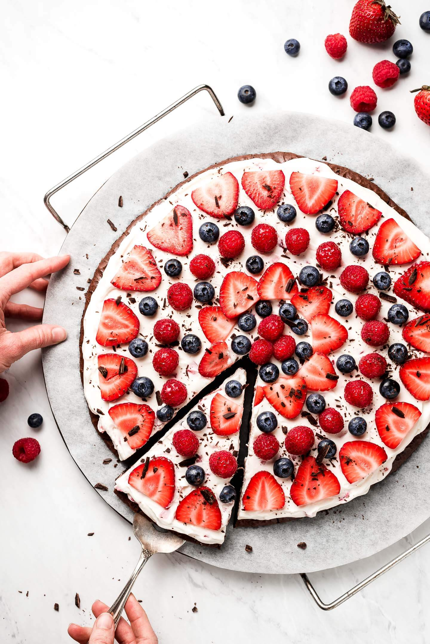 Hand removing a piece of Brownie Fruit Pizza with a cake server.