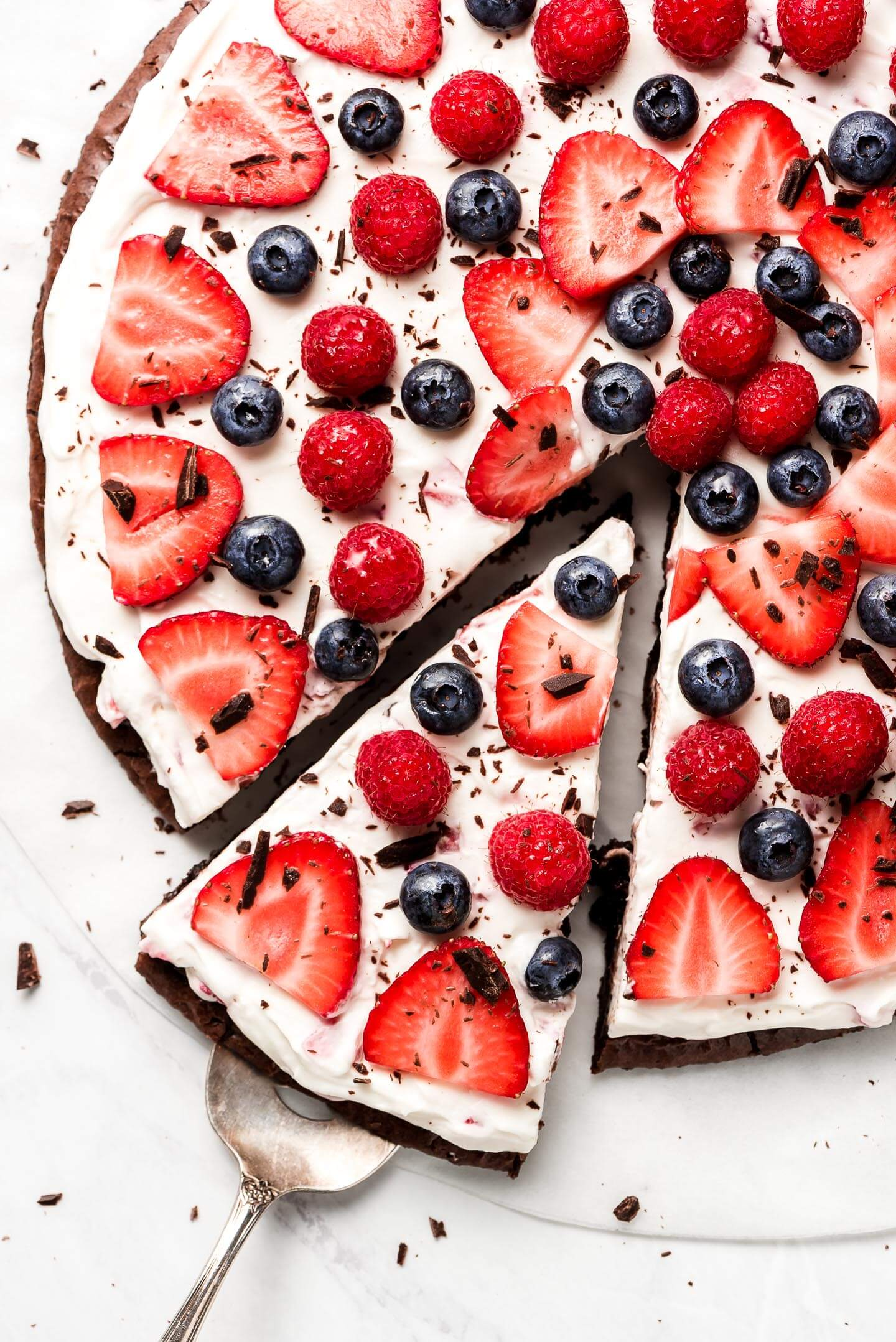 A close up shot of the top of a brownie pizza covered in fresh sliced strawberries, raspberries, and blueberries and sprinkled with finely chopped chocolate.