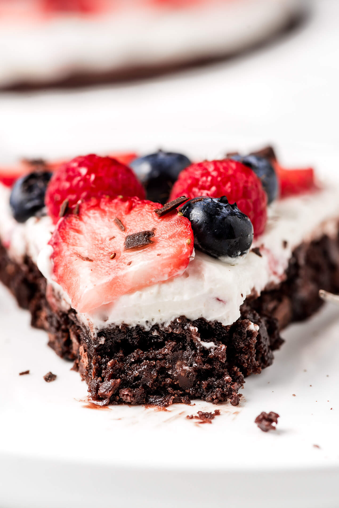 A close up shot of a fudgy brownie covered in cream cheese whipped topping and berries.