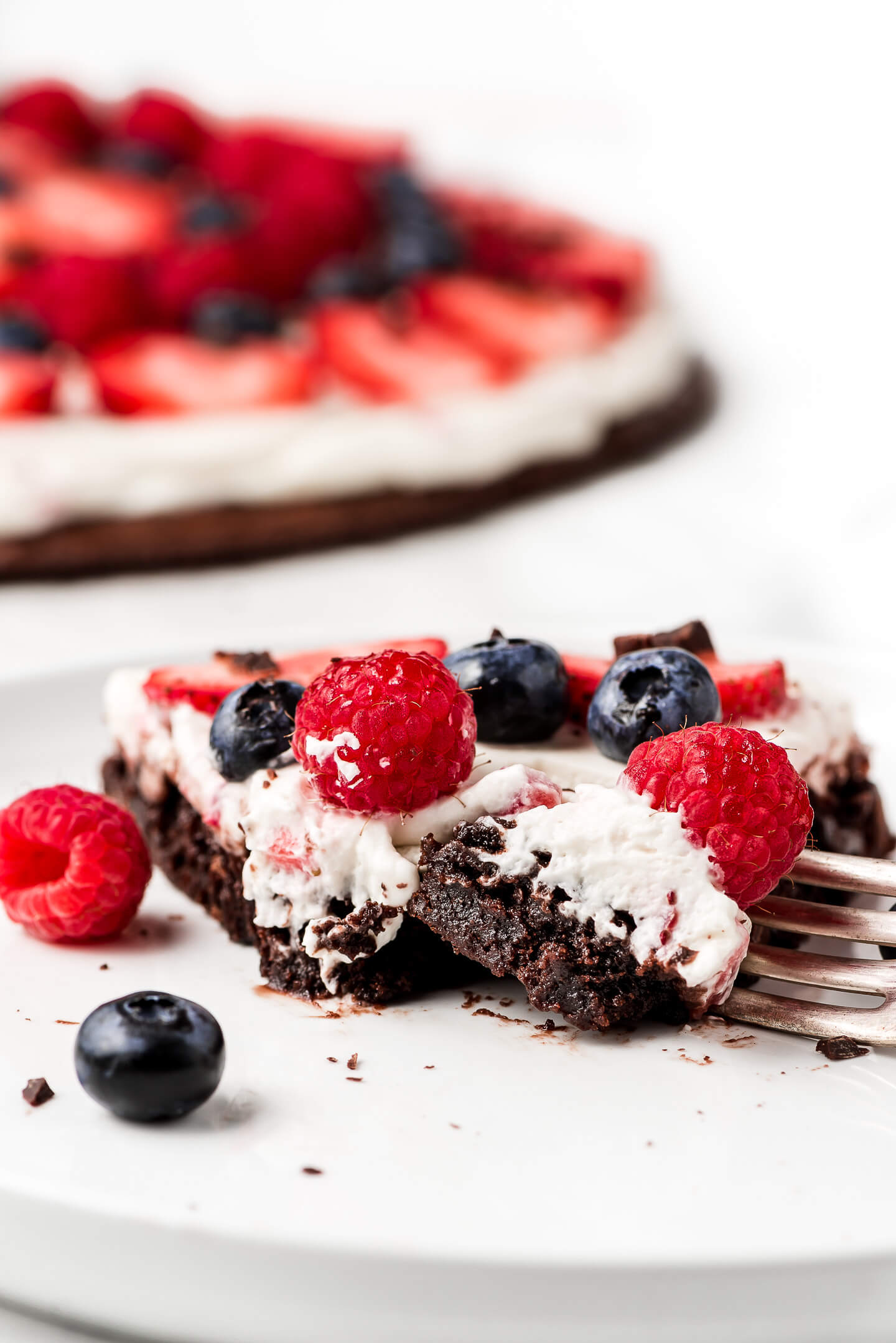 A slice of Berry Brownie Pizza on a plate with a fork cutting into it.