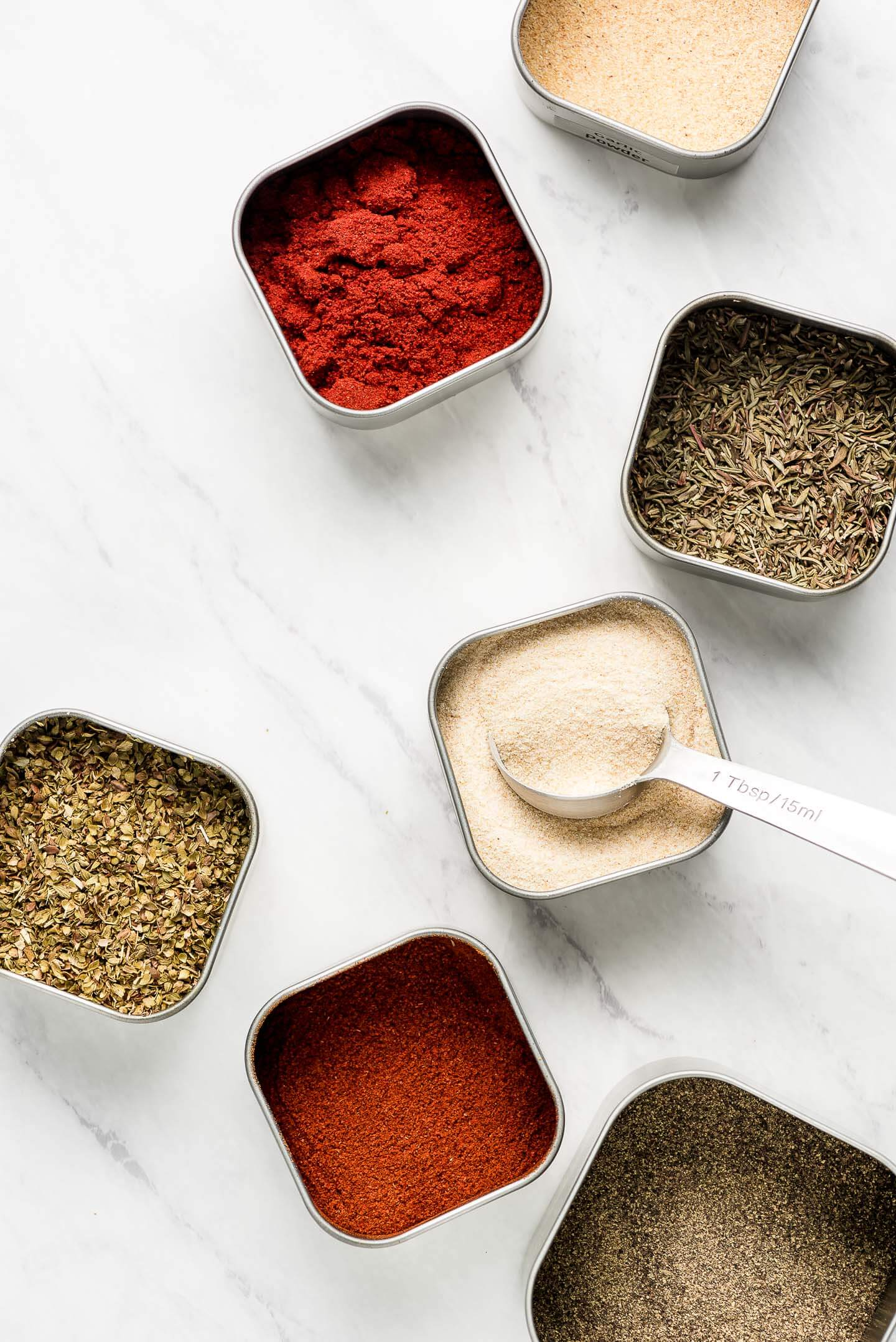 Square tins of herbs and spices on a marble surface.