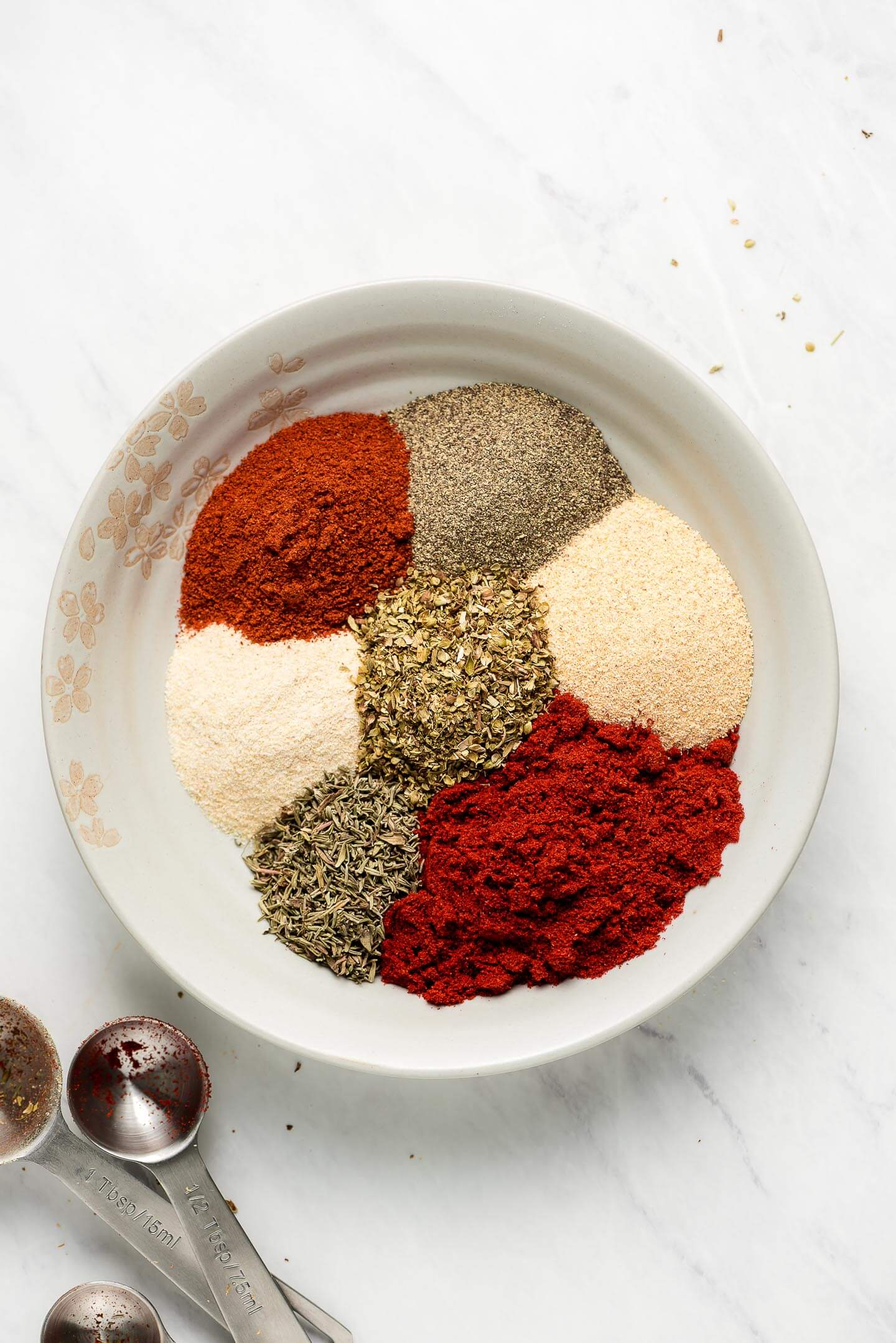 Little piles of spices and herbs in a bowl with measuring spoons to the side.