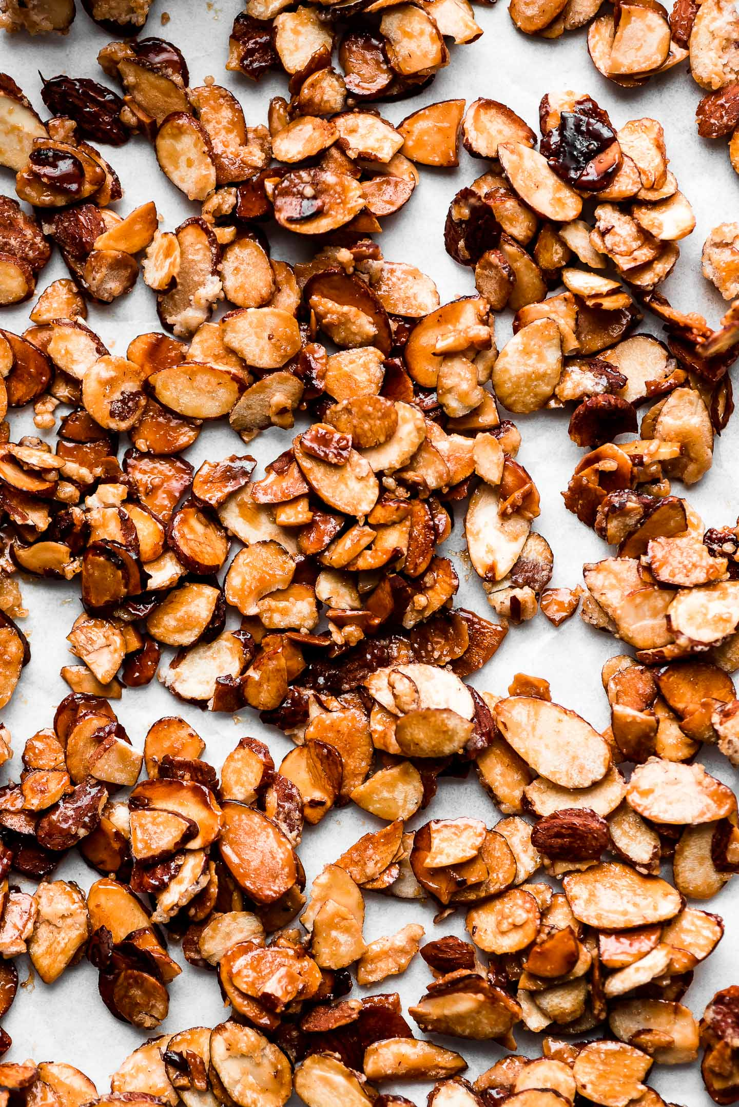 Caramelized sliced almonds spread out on parchment paper.