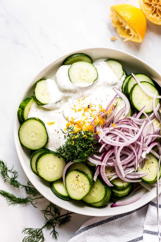 A bowl full of sliced cucumbers, red onions, greek yogurt, lemon zest, and fresh dill.