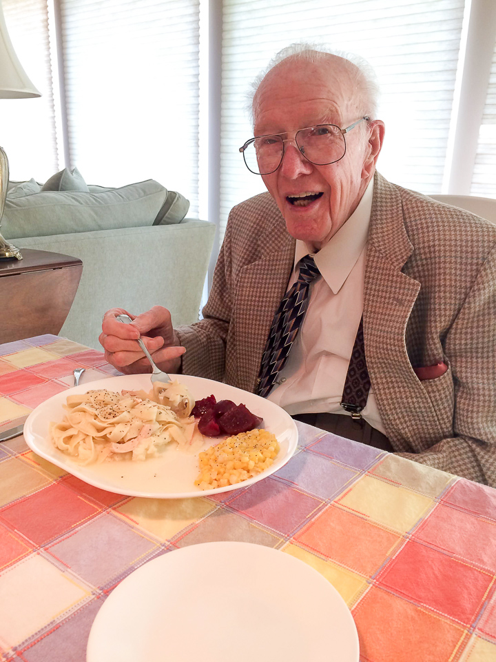 A grandfather eating homemade chicken and noodles over mashed potatoes.