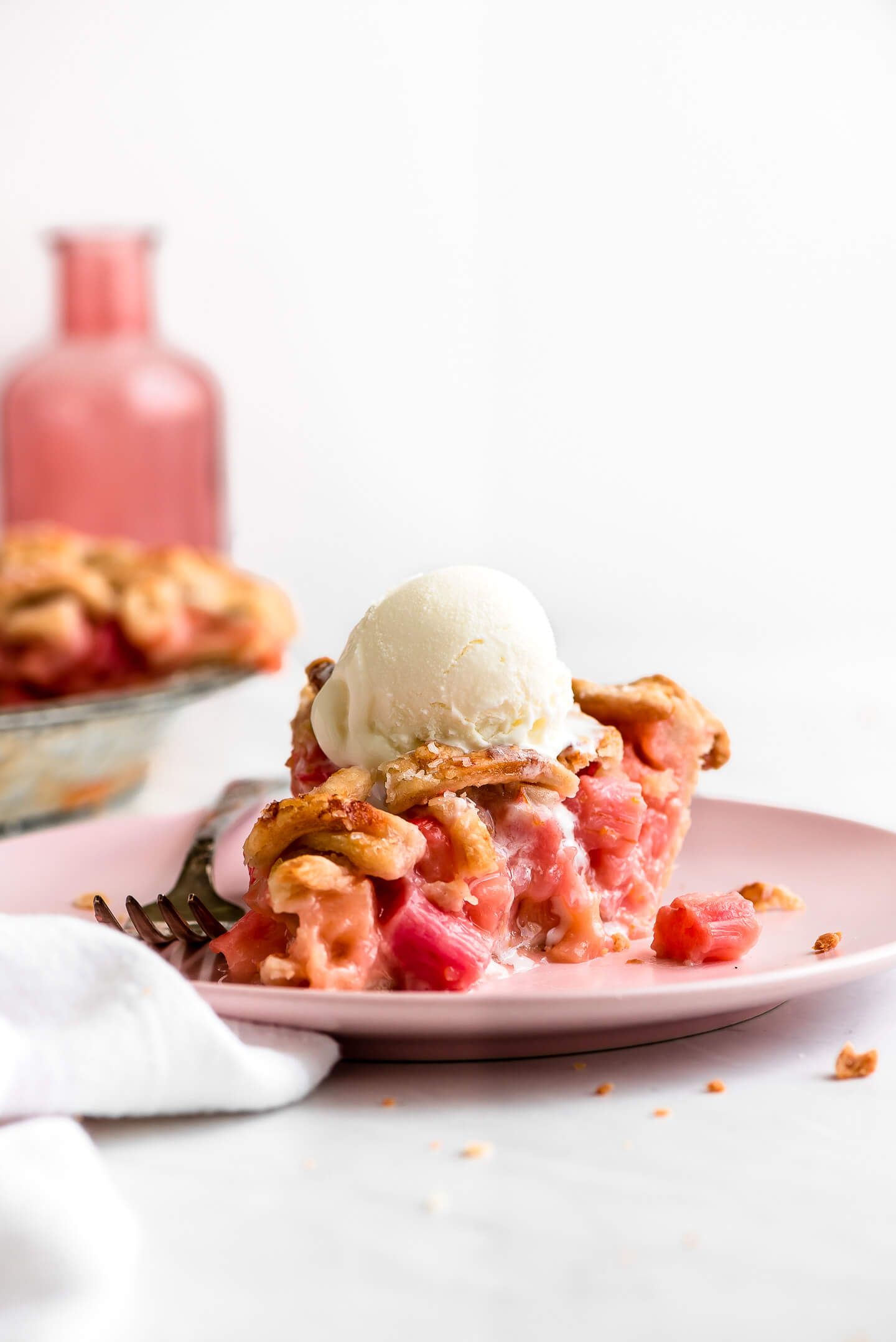 A pink plate with a slice of Rhubarb Pie topped with a scoop of vanilla ice cream.