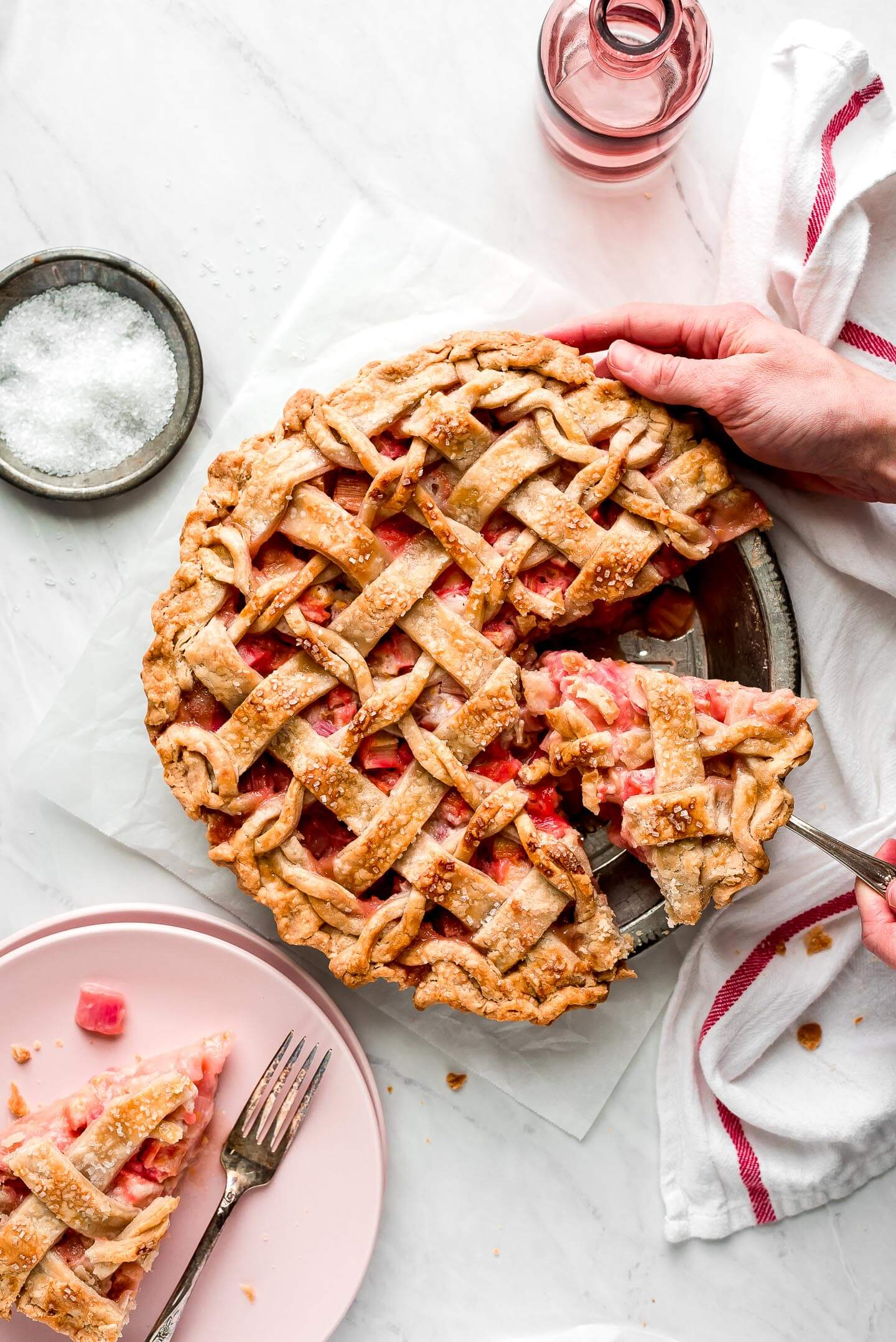 Rhubarb Pie with a lattice top with hands lifting out a slice with a pie server.