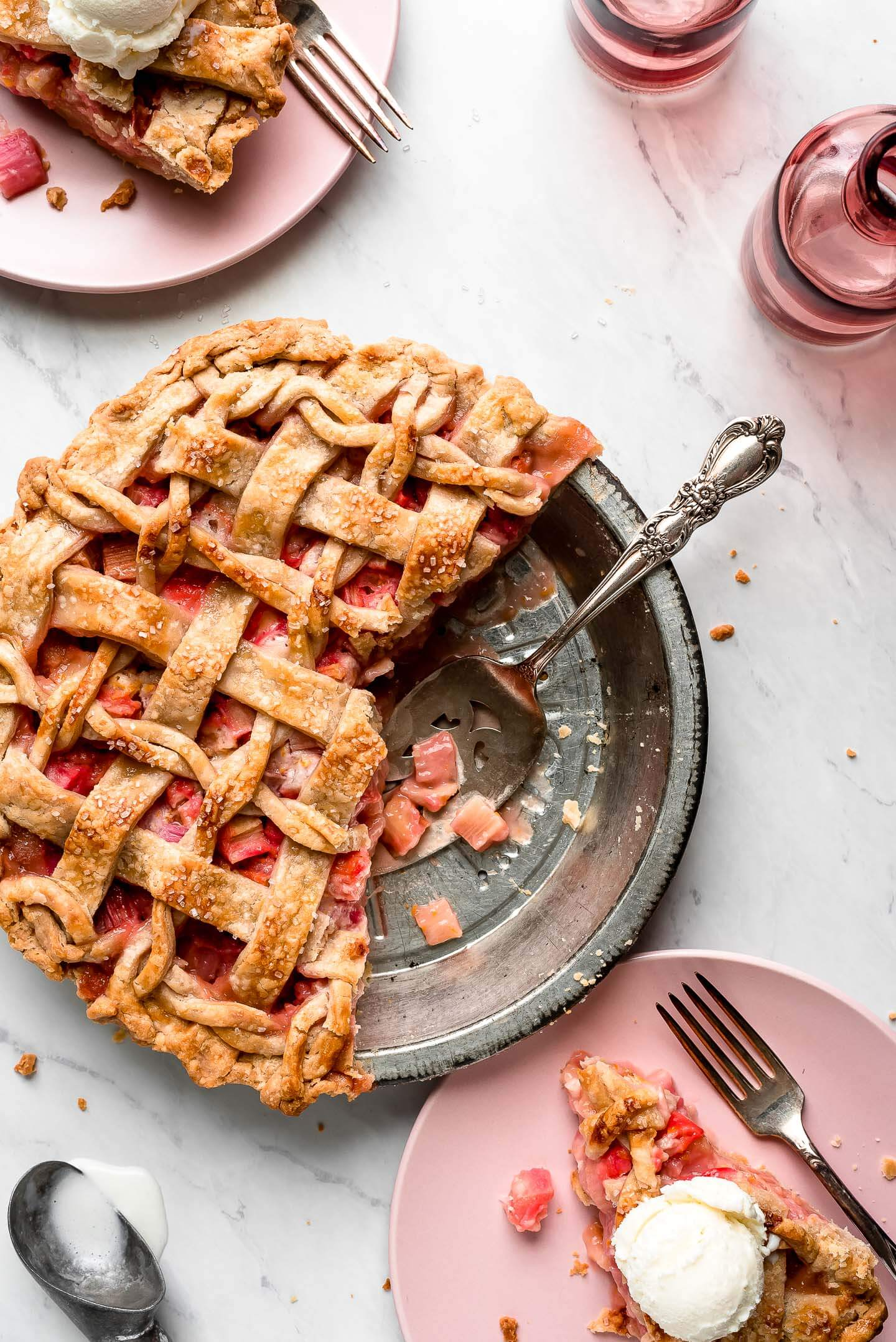 A tin of half a Rhubarb Pie with slices on plates topped with ice cream.