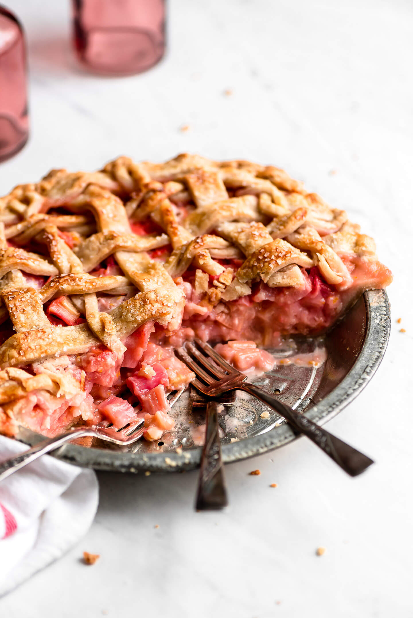 A Rhubarb Pie with slices taken out and forks resting in the pie tin.