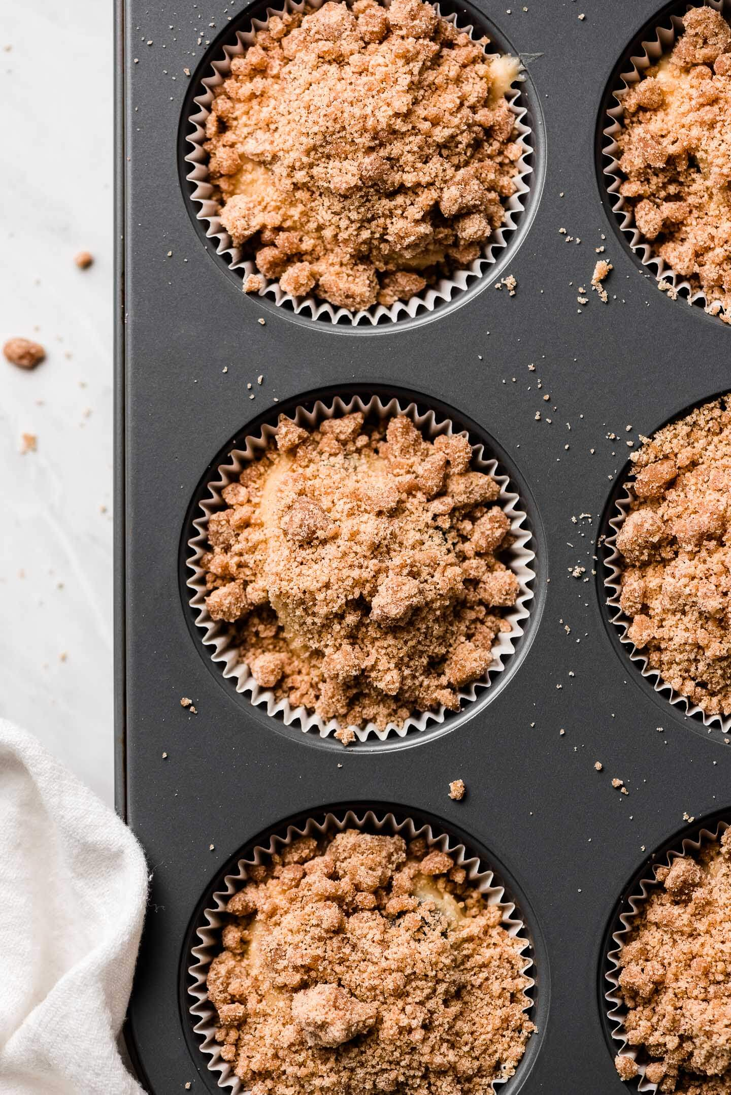A muffin tin with paper liners filled with batter and topped with streusel.