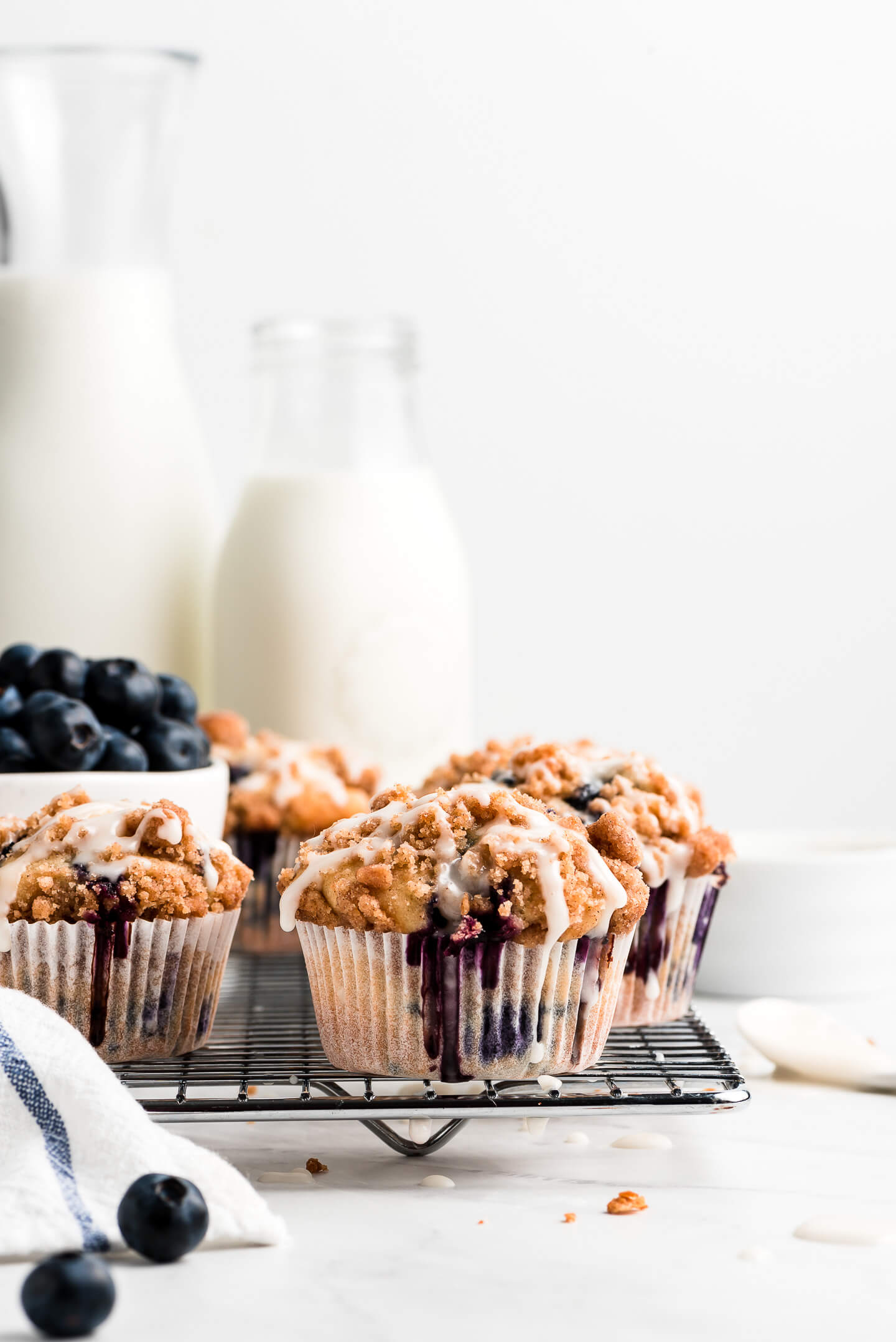 Muffins on a cooling rack with glaze dripping down them and glass bottles of milk in the background.