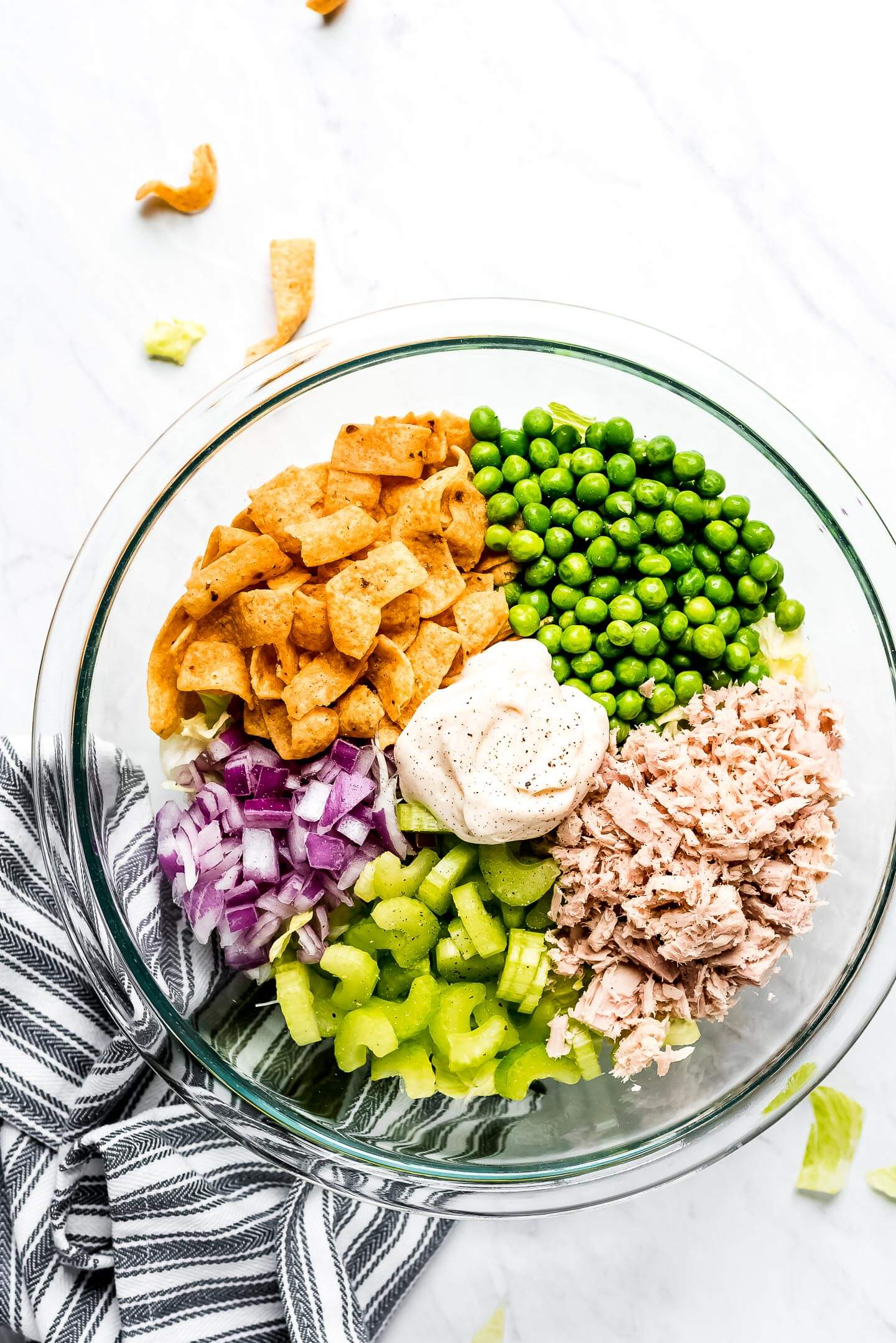 A large mixing bowl with piles of ingredients- Fritos, green peas, tuna fish, celery, and red onion.
