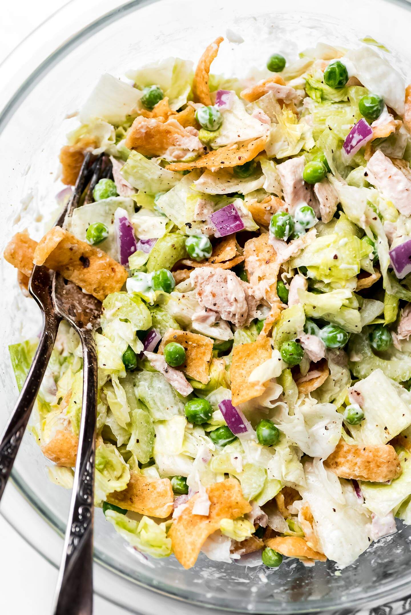 A close up shot of Tuna Chopped Salad in a glass mixing bowl with Fritos, celery, peas, tuna, red onion, and tuna fish.