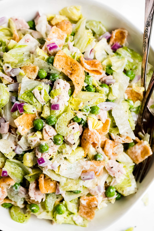 A close-up shot of iceberg lettuce with tuna, peas, celery, and Fritos.