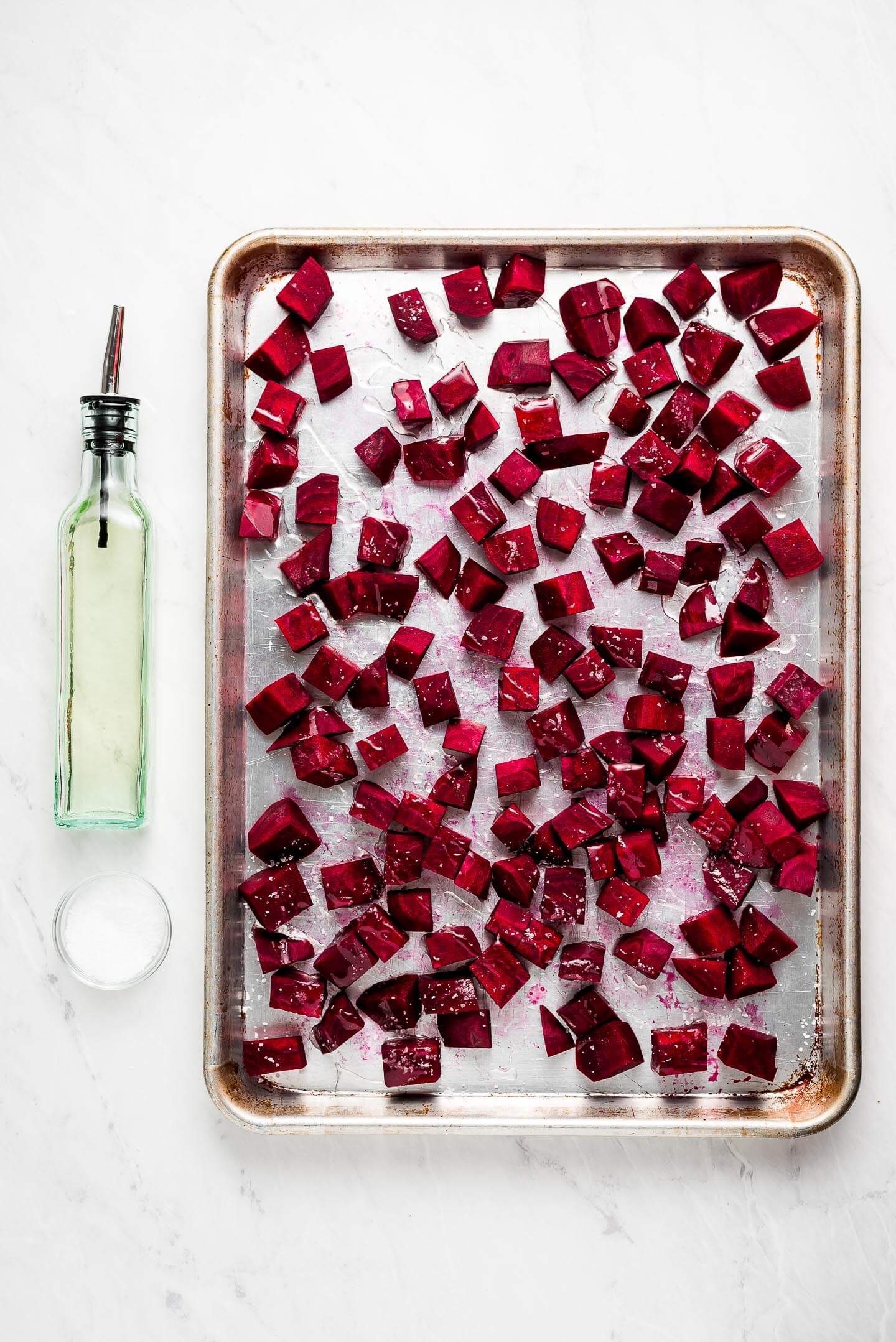 A baking sheet with raw diced beets drizzled with olive oil and sprinkled with kosher salt; a bottle of oil and bowl of salt to the side.