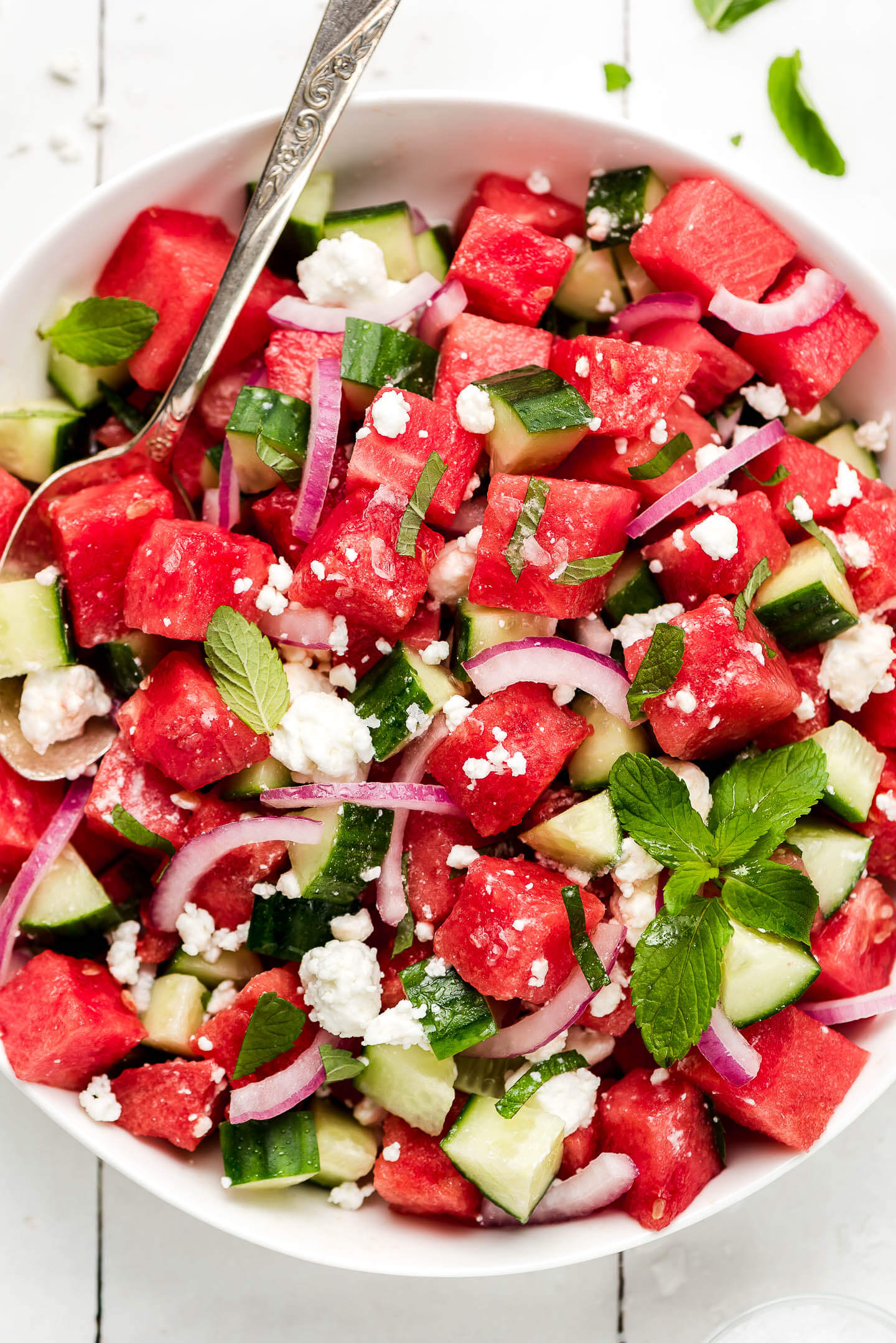 A close up of watermelon cucumber salad with mint, red onion, feta cheese, and salt.