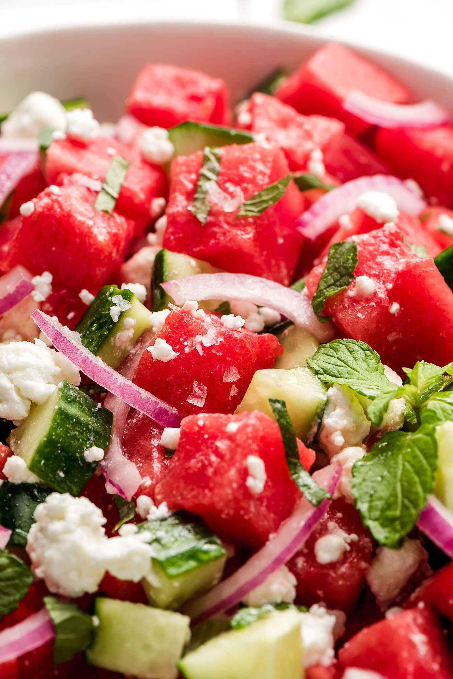 A close up shot of flaky salt and feta cheese on watermelon and cucumber.