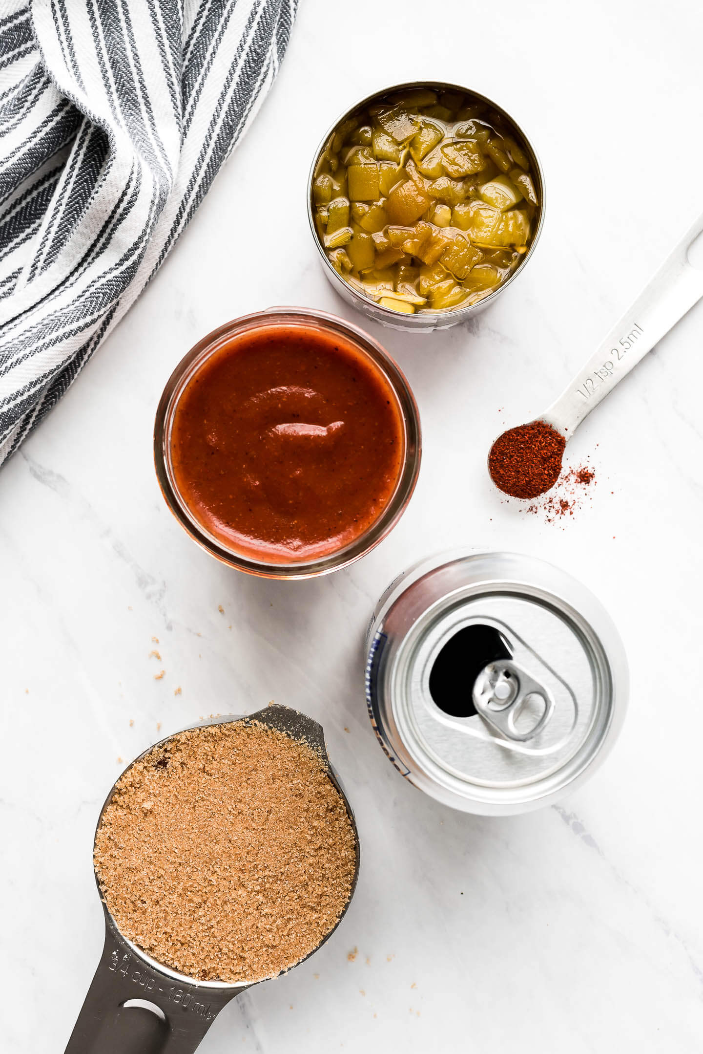 Top view of ingredients- measuring cup of brown sugar, can of soda, enchilada sauce, green chilies, and chili powder.