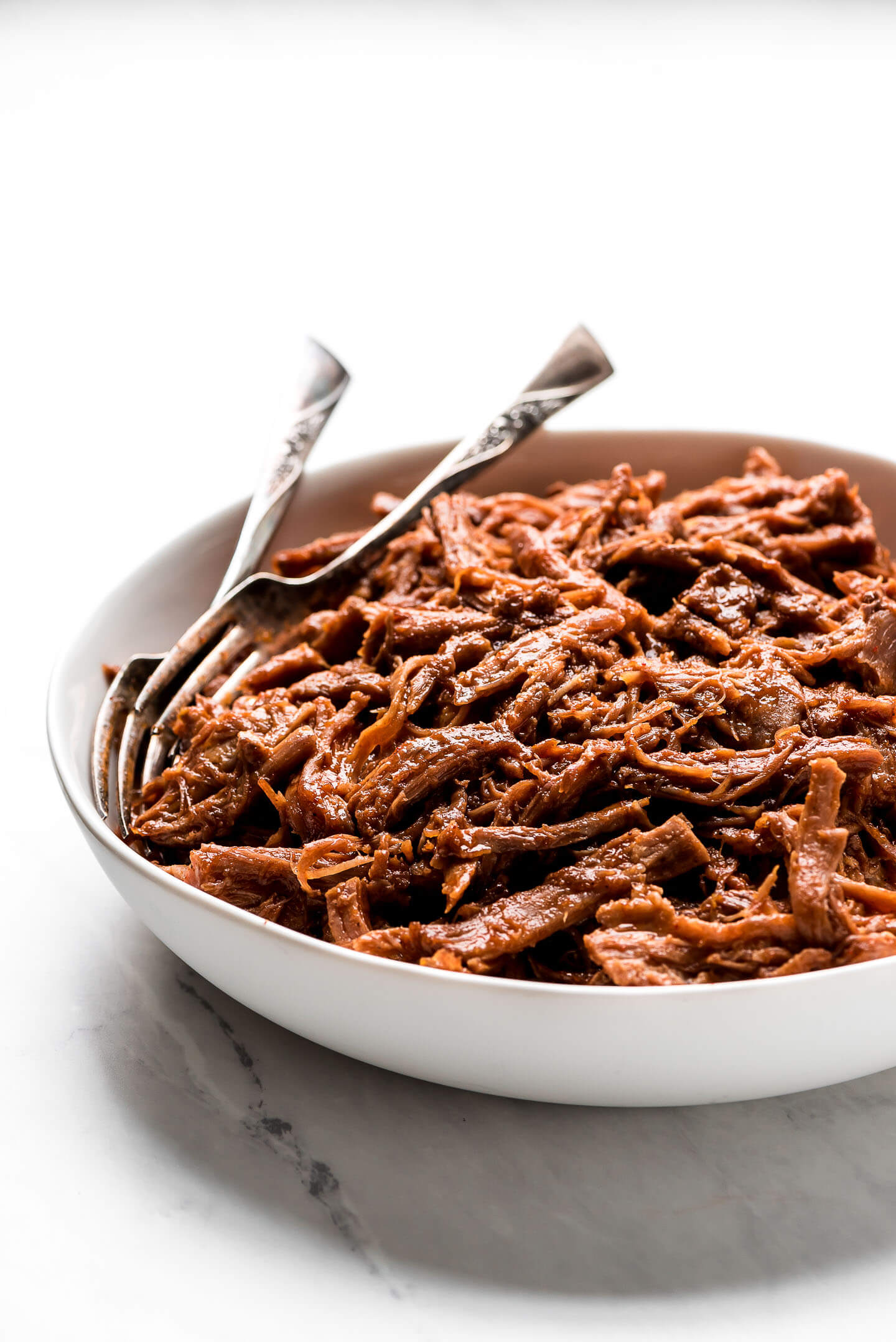 Shredded pork covered in a sauce in a bowl with two forks in the side of the bowl.