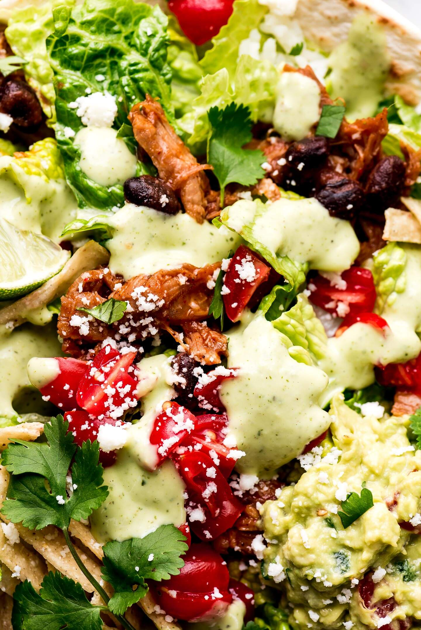 A close-up shot of Cafe Rio Sweet Pork Salad drizzled with creamy Cilantro Lime Dressing.
