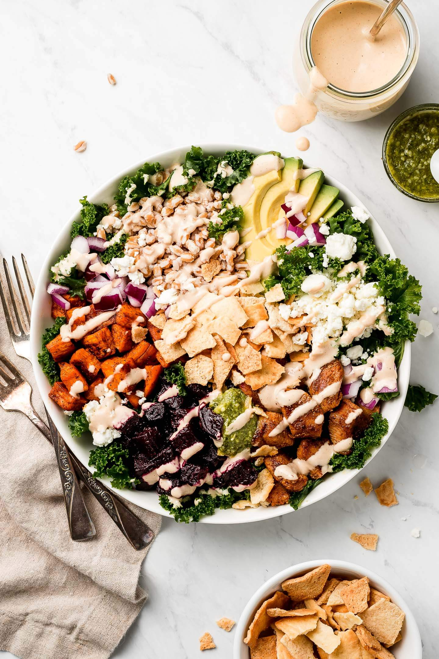 A large bowl of Kale Salad topped with roasted sweet potatoes, beets, farro, avocado, chicken, pita chips, red onions, and goat cheese; a jar of tahini dressing, small bowl of pesto, and bowl or pita chips to the side.