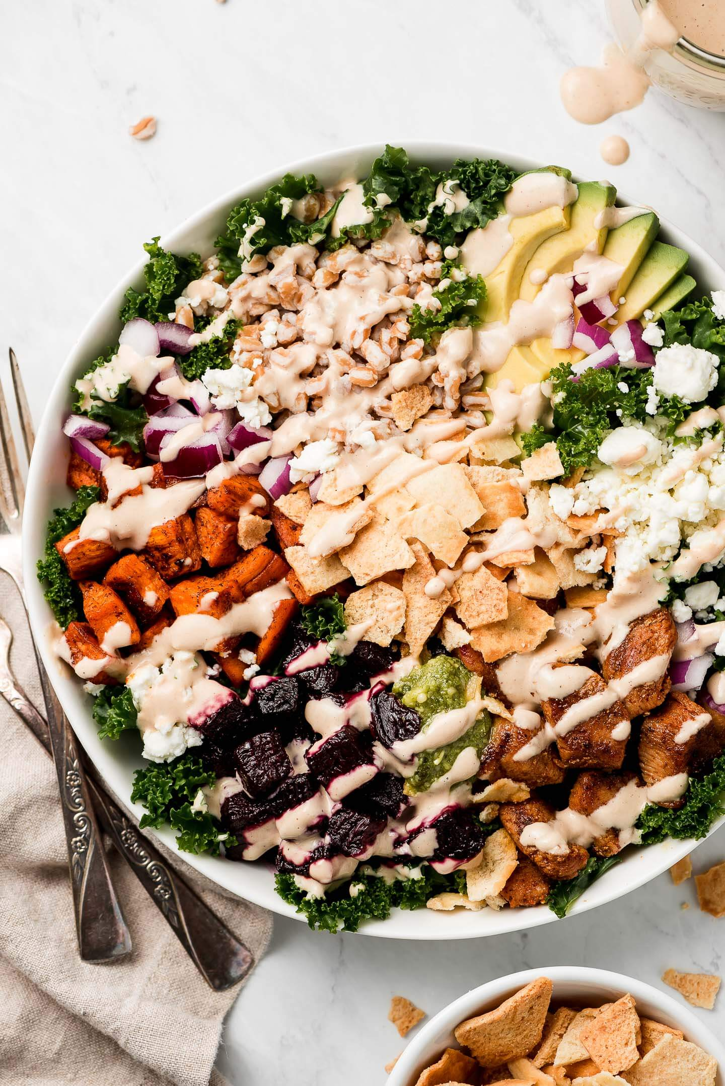 A kale salad with vegetables, chicken, farro, cheese, and avocado drizzled with tahini dressing.