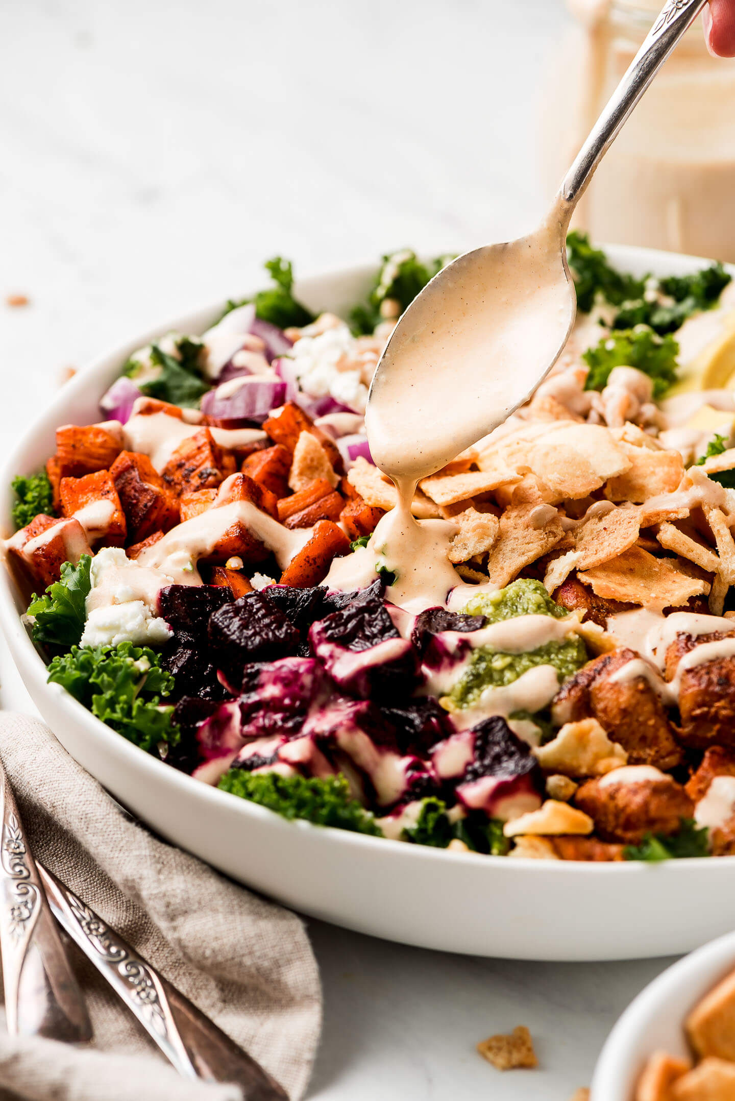 Spooning tahini dressing over a kale salad.
