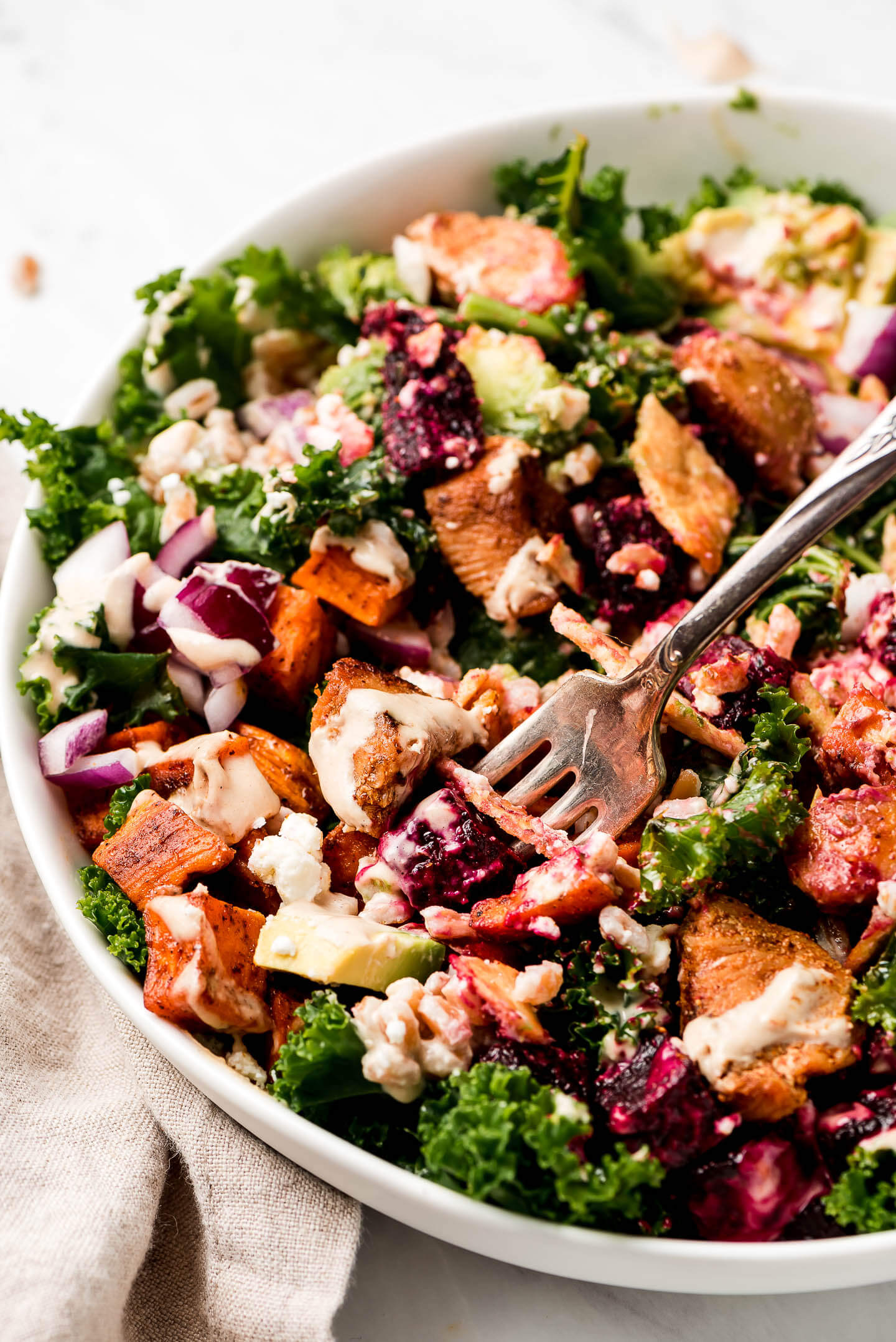 A close up photo of a tossed Kale Salad with Roasted Vegetables.