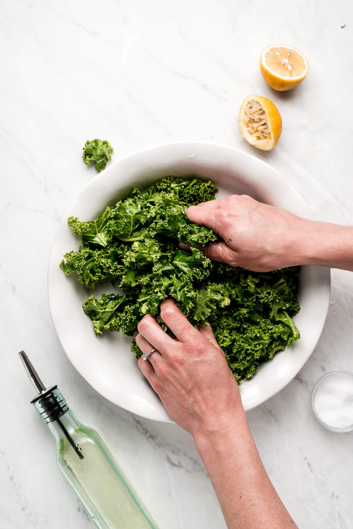 Photo showing how to massage kale by grabbing it in hands and rubbing it between fingers.