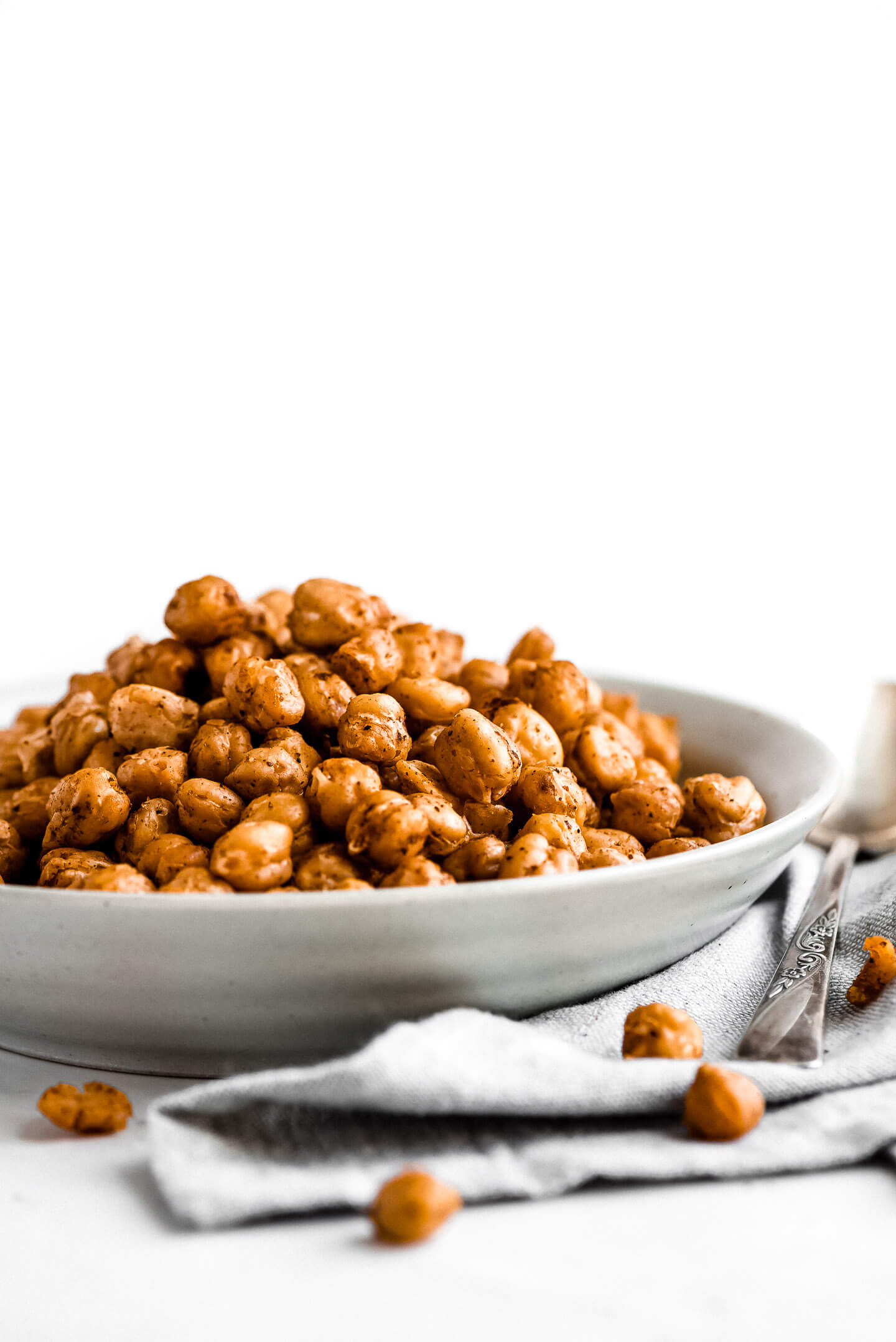 Crispy seasoned chickpeas piled high in a bowl with a spoon to the side on a gray cloth napkin.