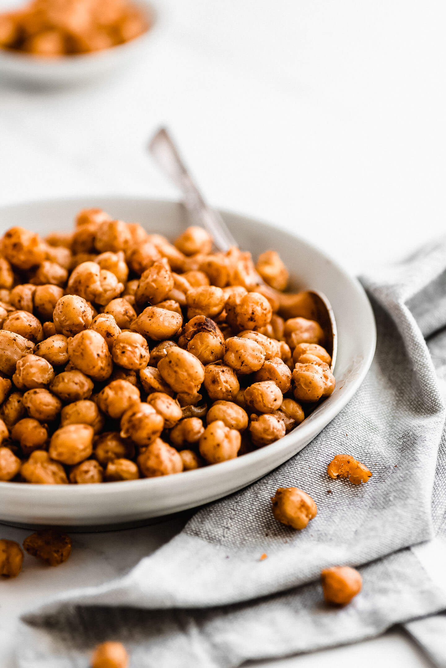 Crispy Roasted Chickpeas in a gray bowl with a spoon in the side and a napkin underneath with a few chickpeas on it.