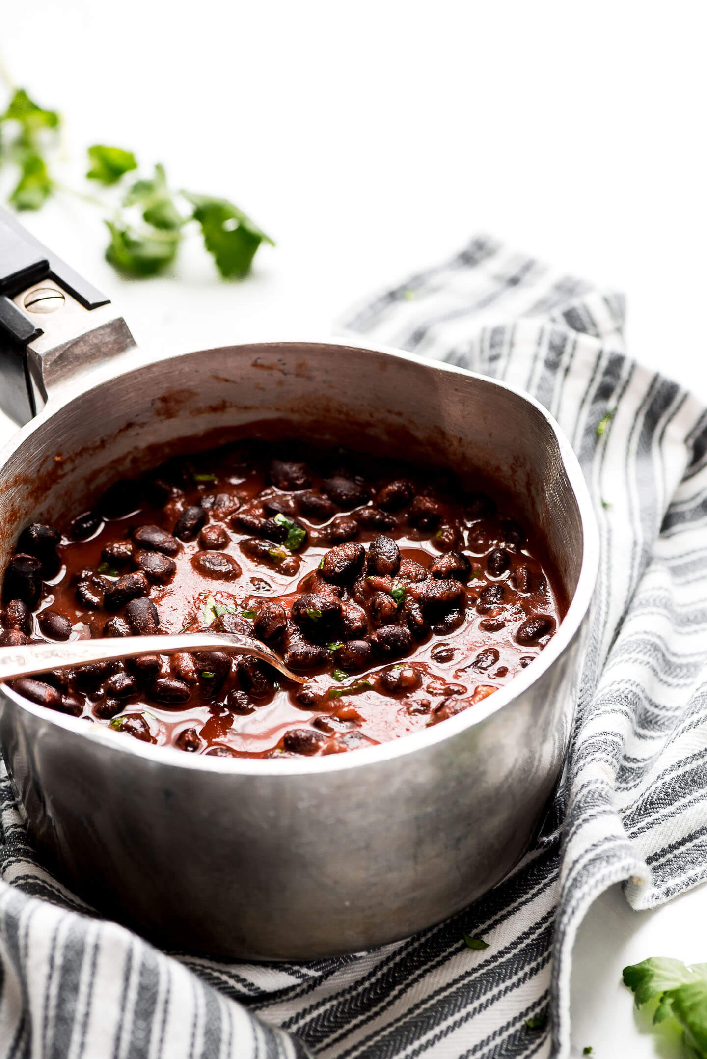 Seasoned Black Beans in a small pot with a spoon lifting some out.
