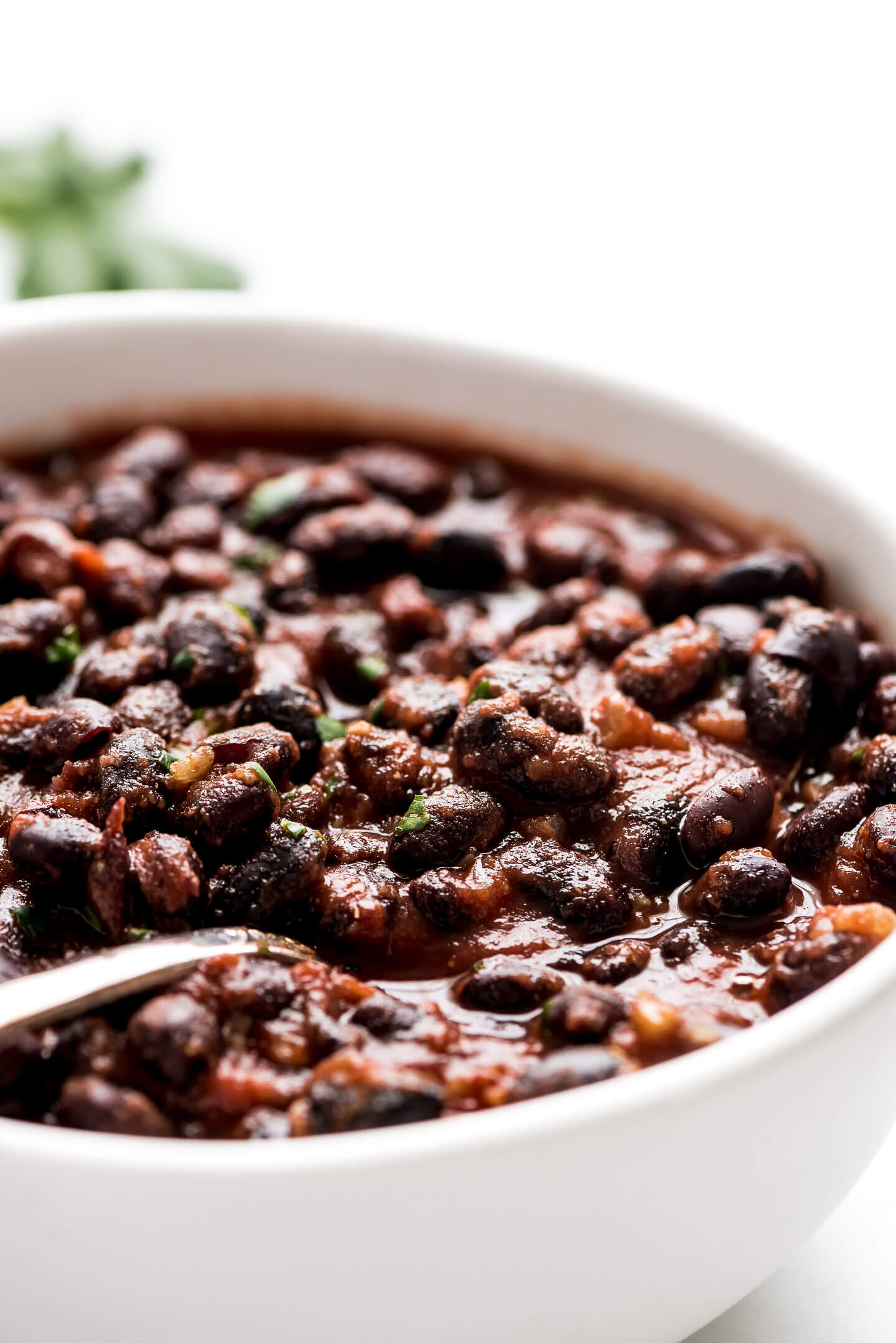 A close-up photo of seasoned black beans in a white bowl.