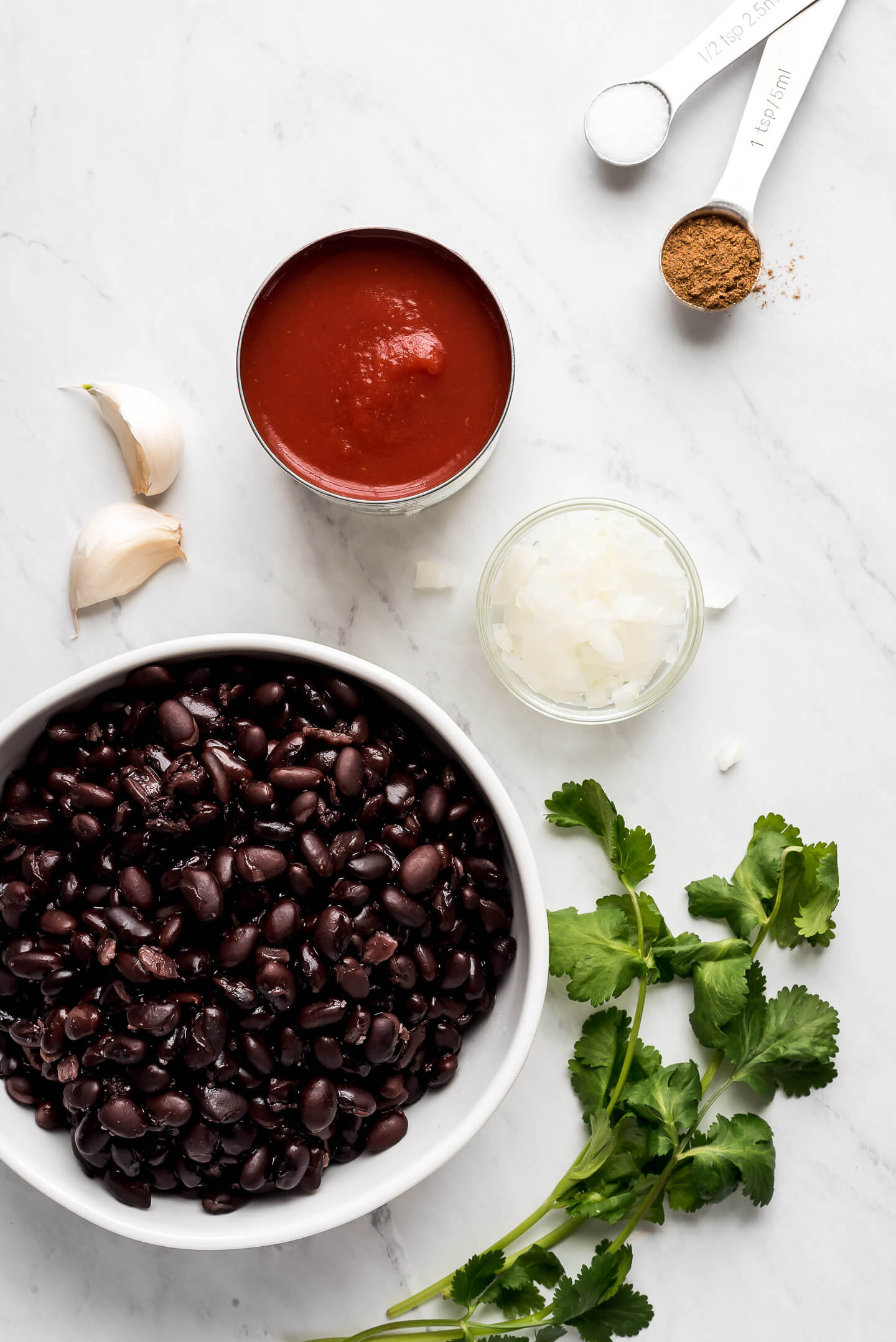 A large bowl of beans, a can of tomato sauce, a small bowl of chopped onions, cloves of garlic, fresh cilantro, and measuring spoons of spices laying on a marble surface.