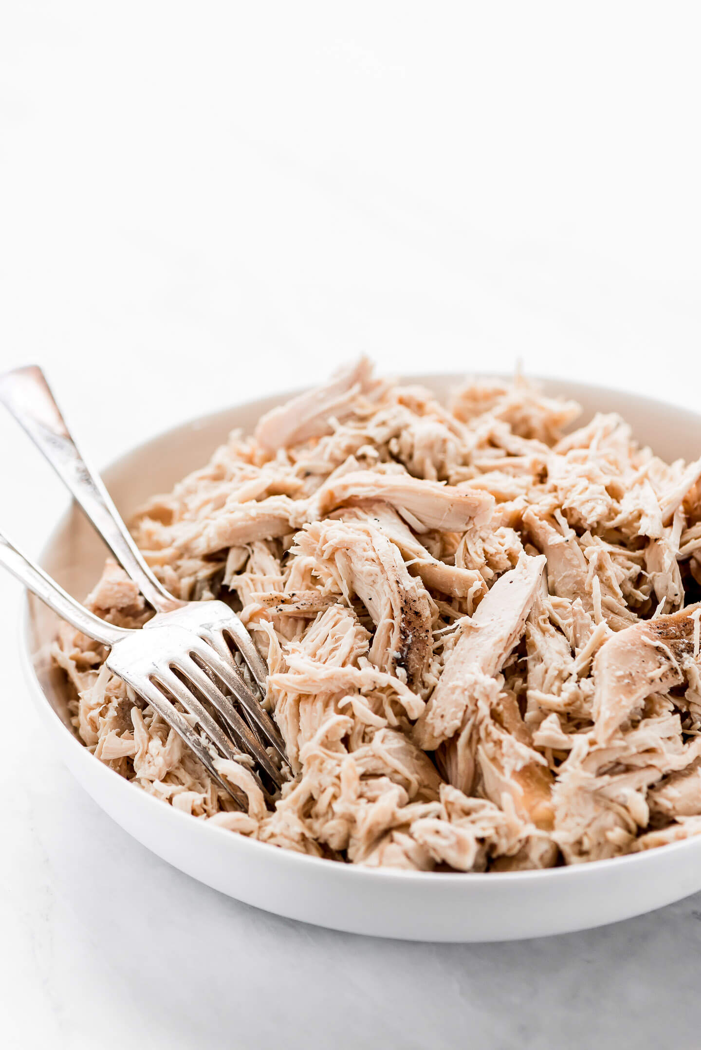 Slow Cooker Shredded Chicken in a large white serving bowl with two forks in the side.