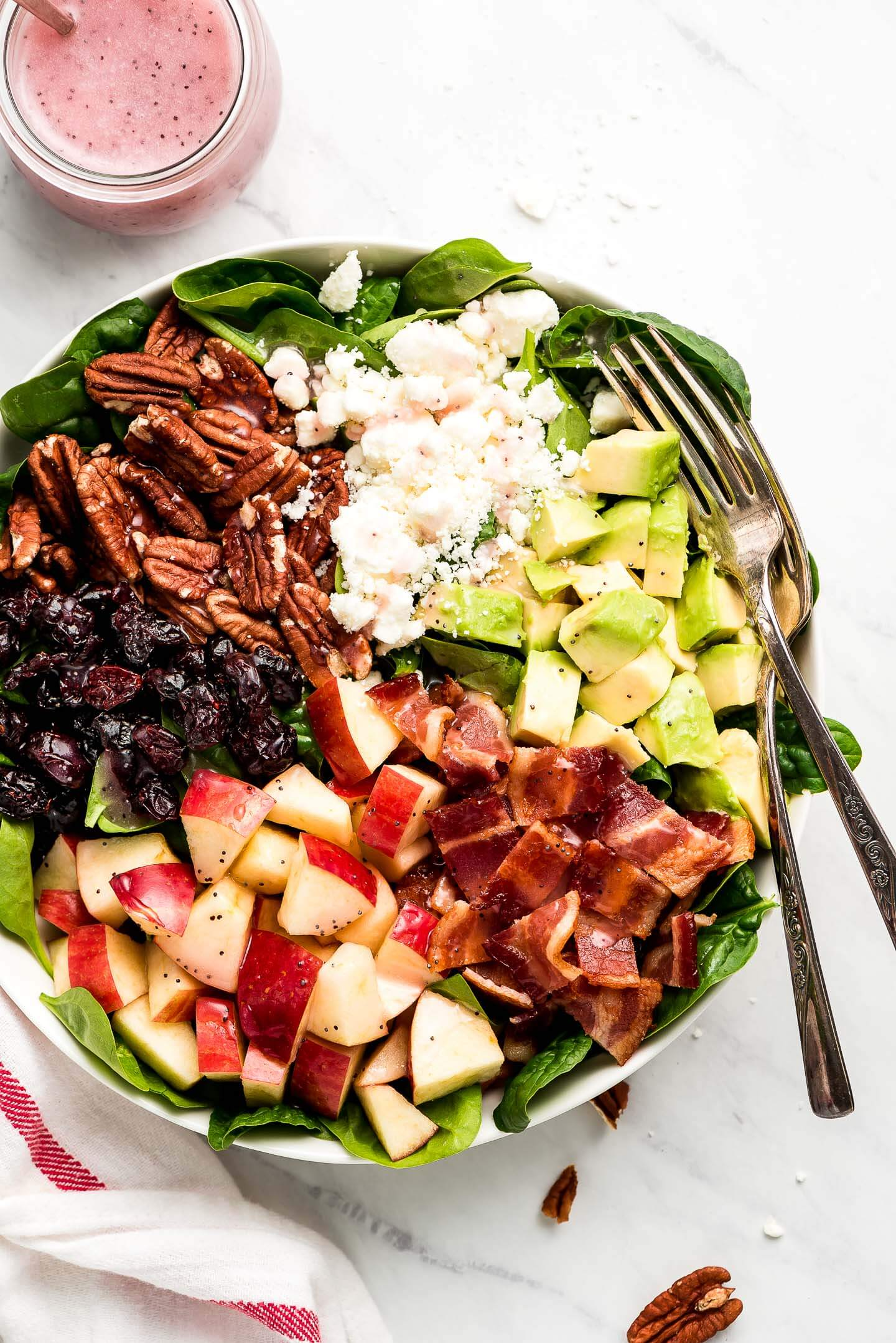 A bowl of baby spinach topped with pecans, feta cheese, diced avocado, chopped bacon, diced apple, and dried cranberries.