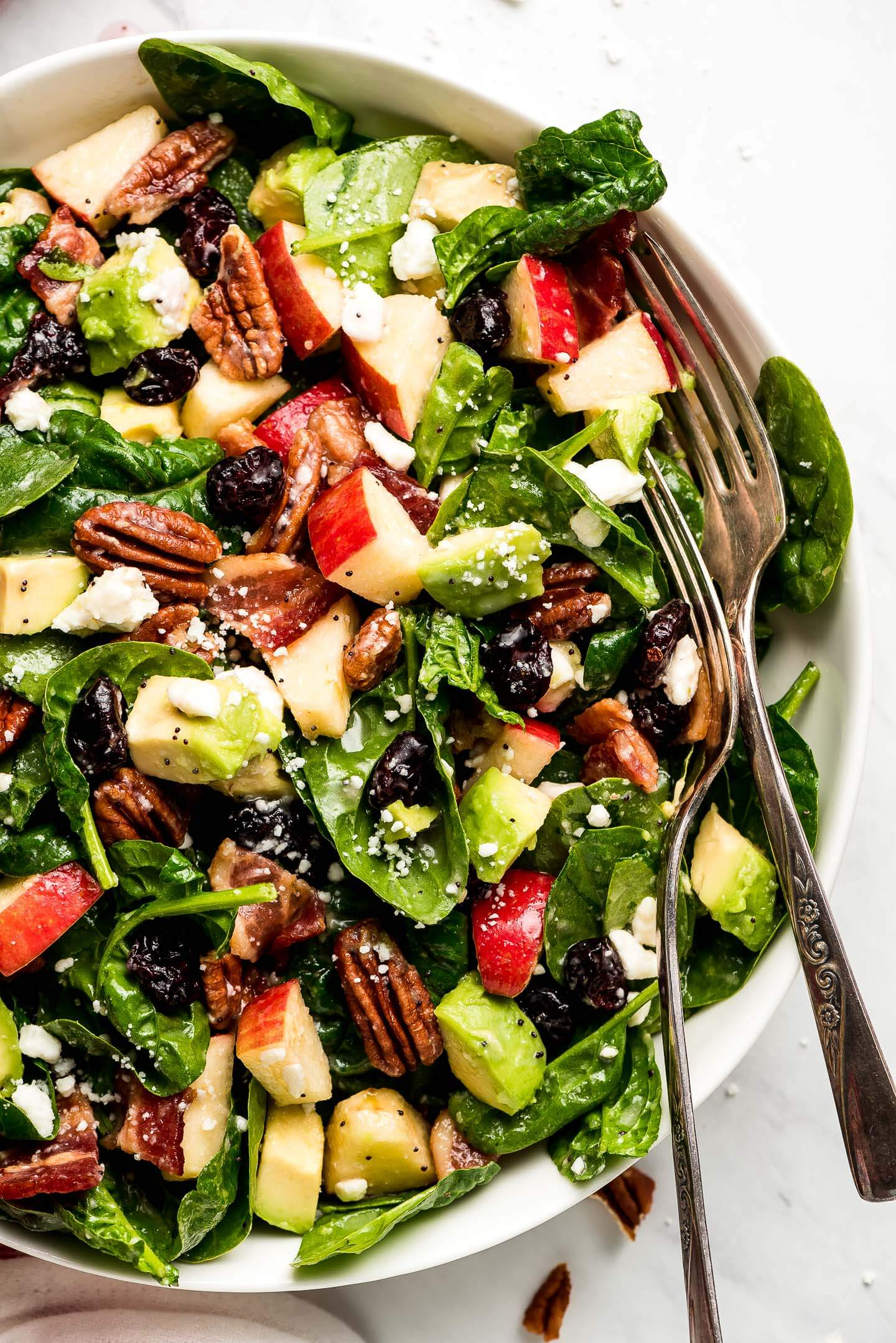 Close-up top view of a spinach salad loaded with toasted pecans, apples, avocado, dried cranberries, bacon, and feta cheese.