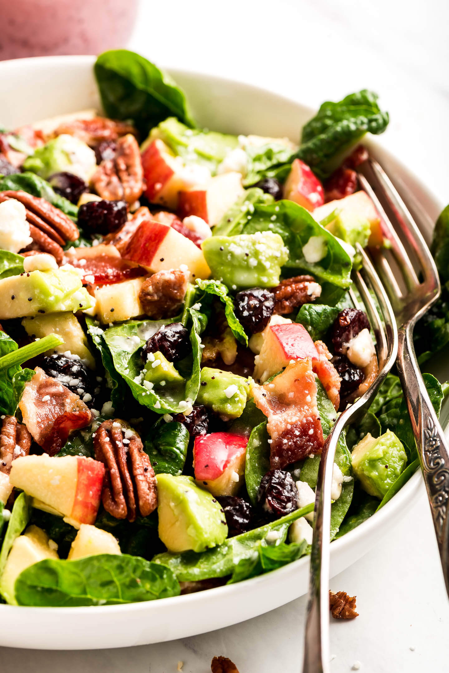 A close-up shot of Apple & Bacon Spinach Salad tossed in poppy seed dressing with two forks in the side of the bowl.