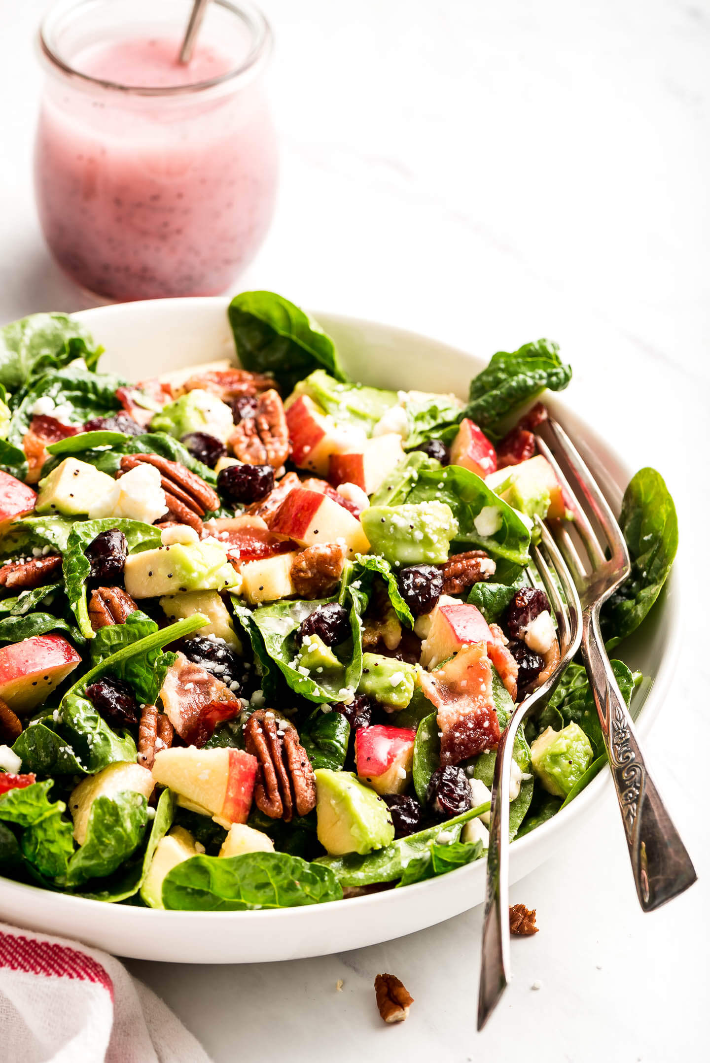 A tossed poppy seed spinach salad with two fork in the bowl with a jar of poppy seed dressing in the background.
