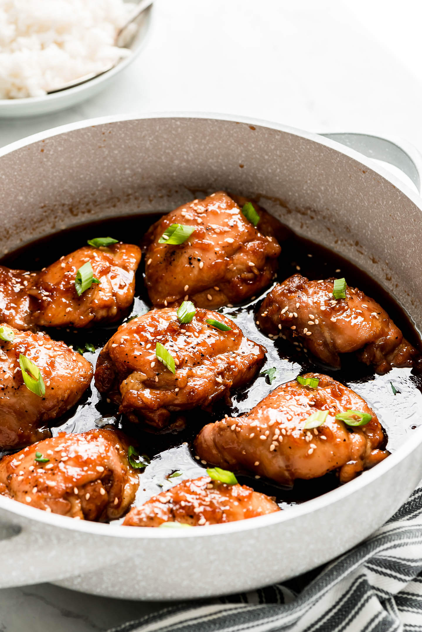Teriyaki Chicken Thighs in a pan with sauce and garnished with sesame seeds and green onions.