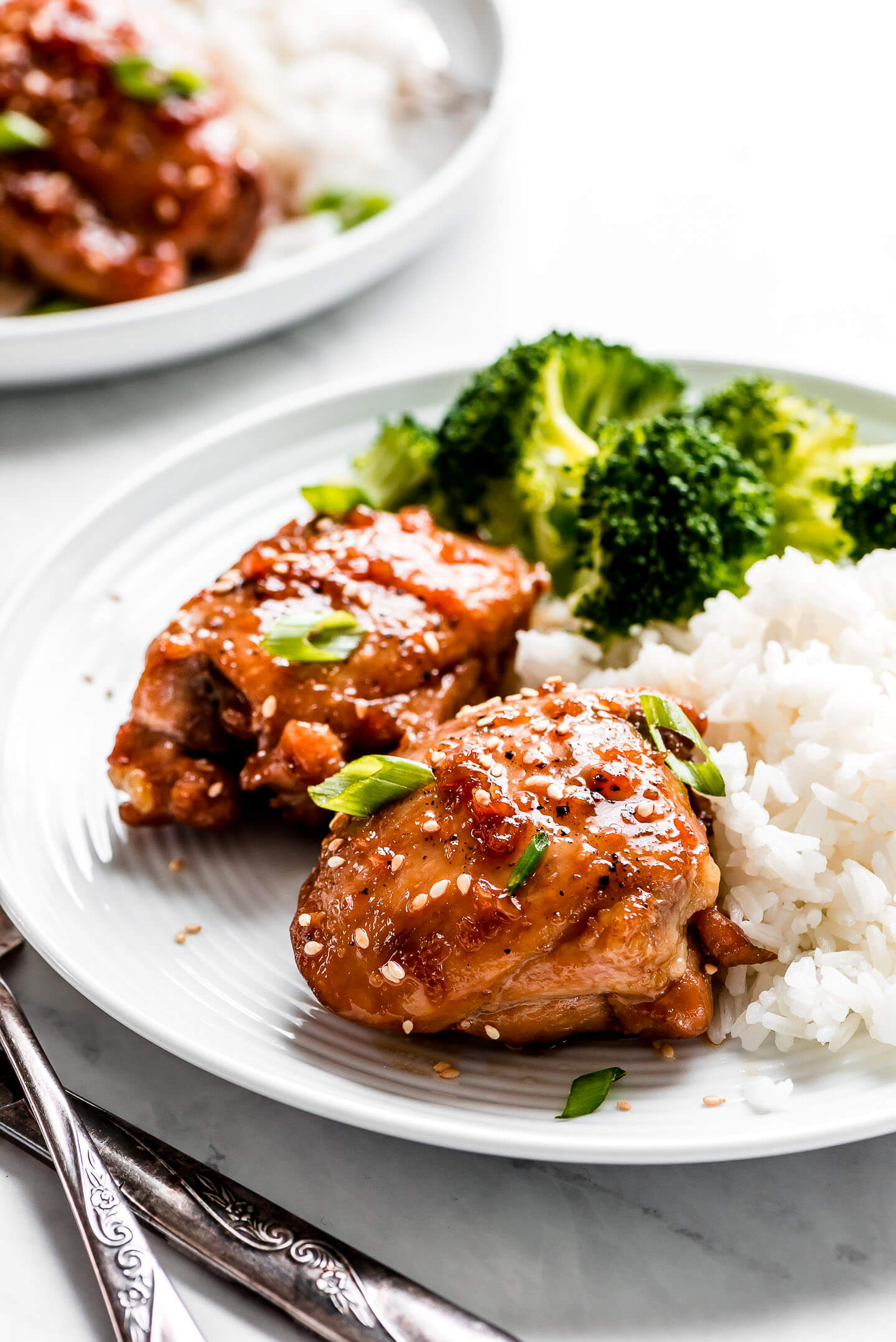 Teriyaki Chicken Thighs garnished with green onions on a white plate with white rice and broccoli.